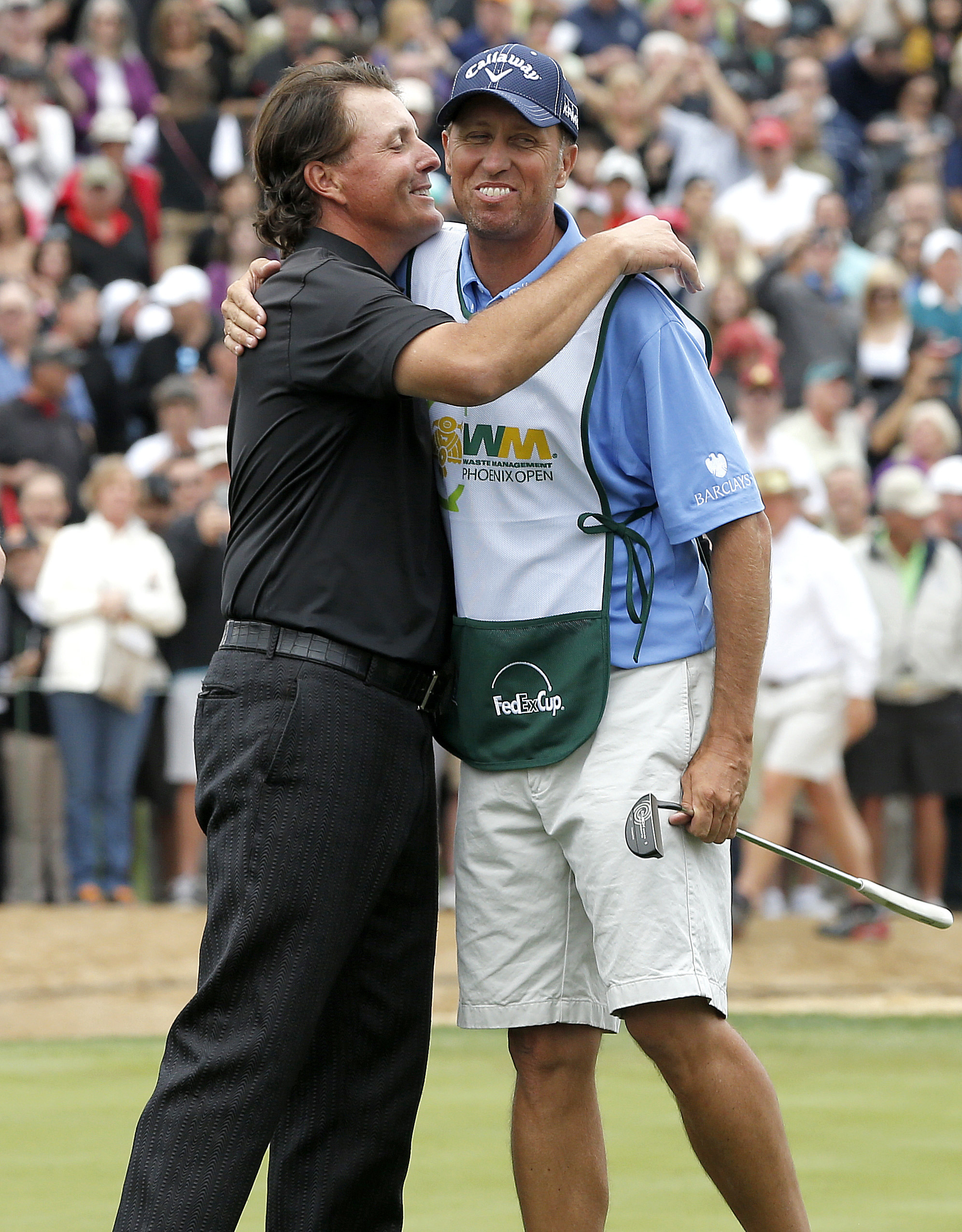 FILE - In this Feb. 3, 2013, file photo, Phil Mickelson, left, hugs his caddie, Jim Mackay, after winning the Phoenix Open golf tournament, in Scottsdale, Ariz. Mickelson and his caddie have decided to part ways after 25 years of one of the most famous pl
