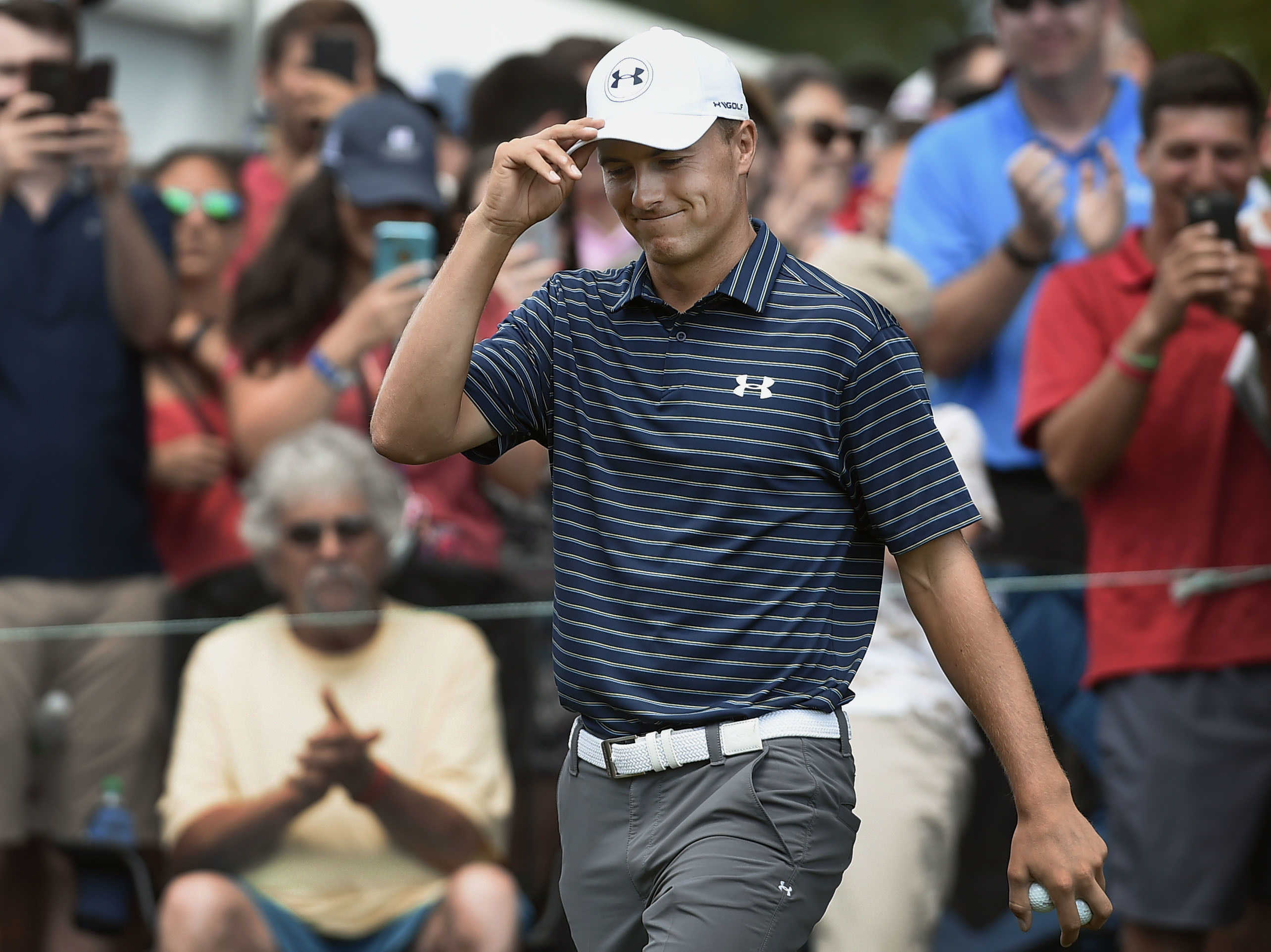 Jordan Spieth tips his hat to fans as he is introduced at the first hole during the final round of the Travelers Championship golf tournament, Sunday, June 25, 2017, in Cromwell, Conn. (AP Photo/Jessica Hill)