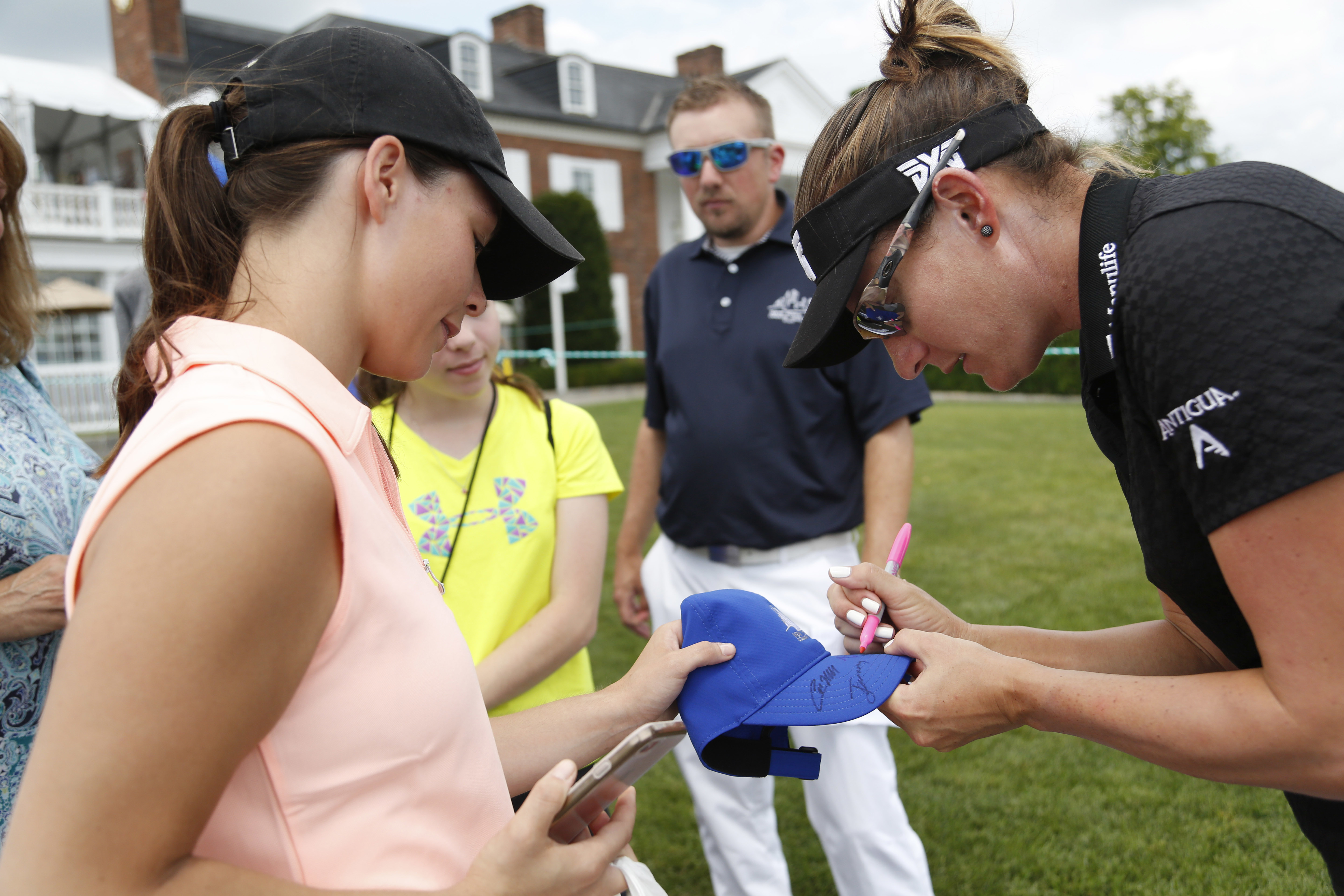 Brittany Lang signs a hat for a fan during a practice round for the U.S. Women's Open Golf Championship at Trump National Golf Club in Bedminster, N.J., Wednesday, July 12, 2017. (AP Photo/Seth Wenig)