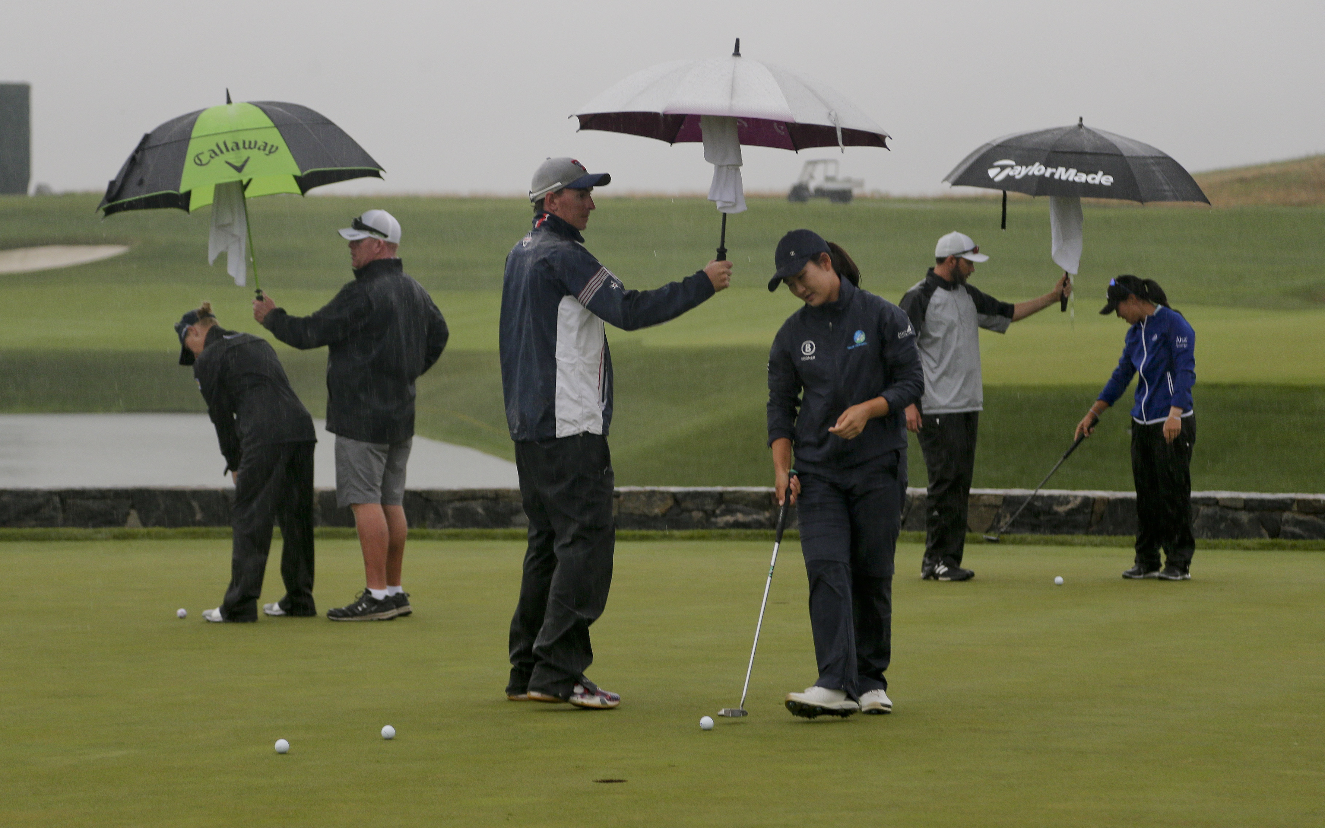 Players putt on the practice green atf the U.S. Women's Open Golf tournament Friday, July 14, 2017, in Bedminster, N.J. A rain delay Thursday pushed back the start of the second round. (AP Photo/Seth Wenig)