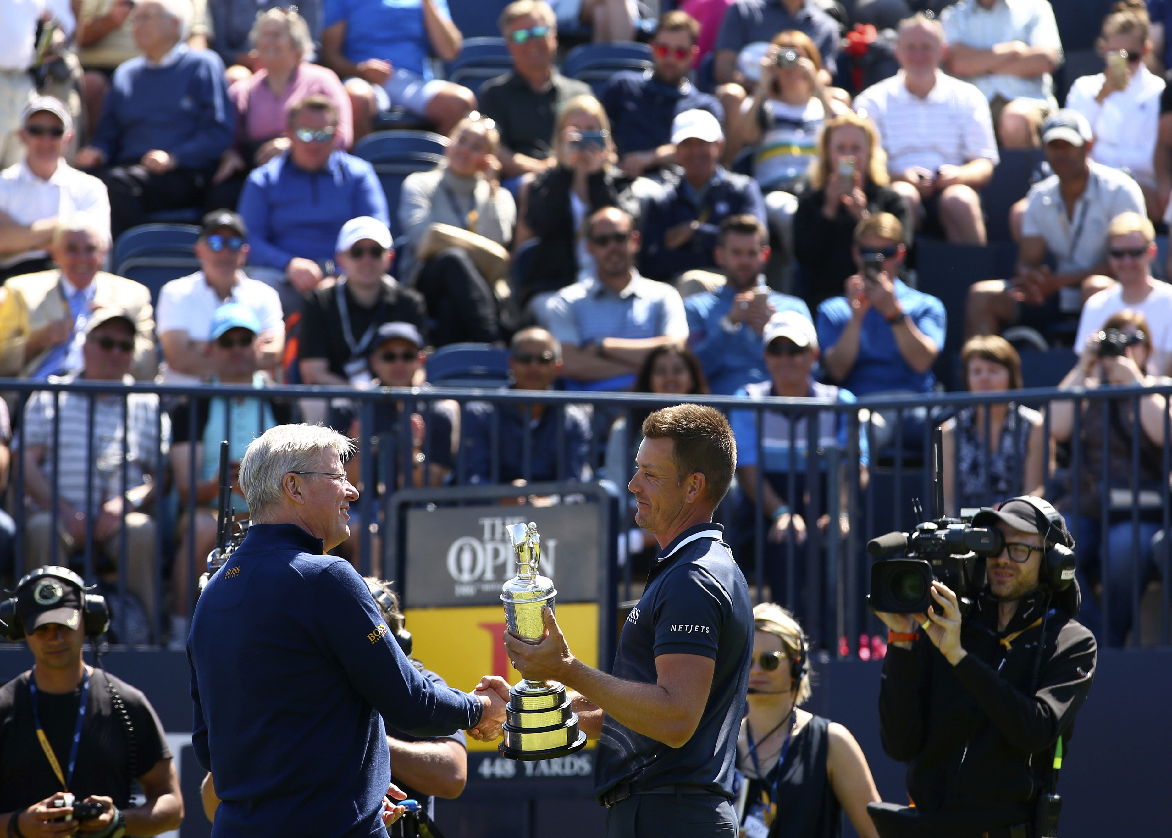 Defending champion Henrik Stenson of Sweden, right, hands over the Claret Jug to Martin Slumbers, Chief Executive of the R&A, during the second practice day at the British Open Golf Championship at Royal Birkdale in Southport, England, Monday, July 17, 20