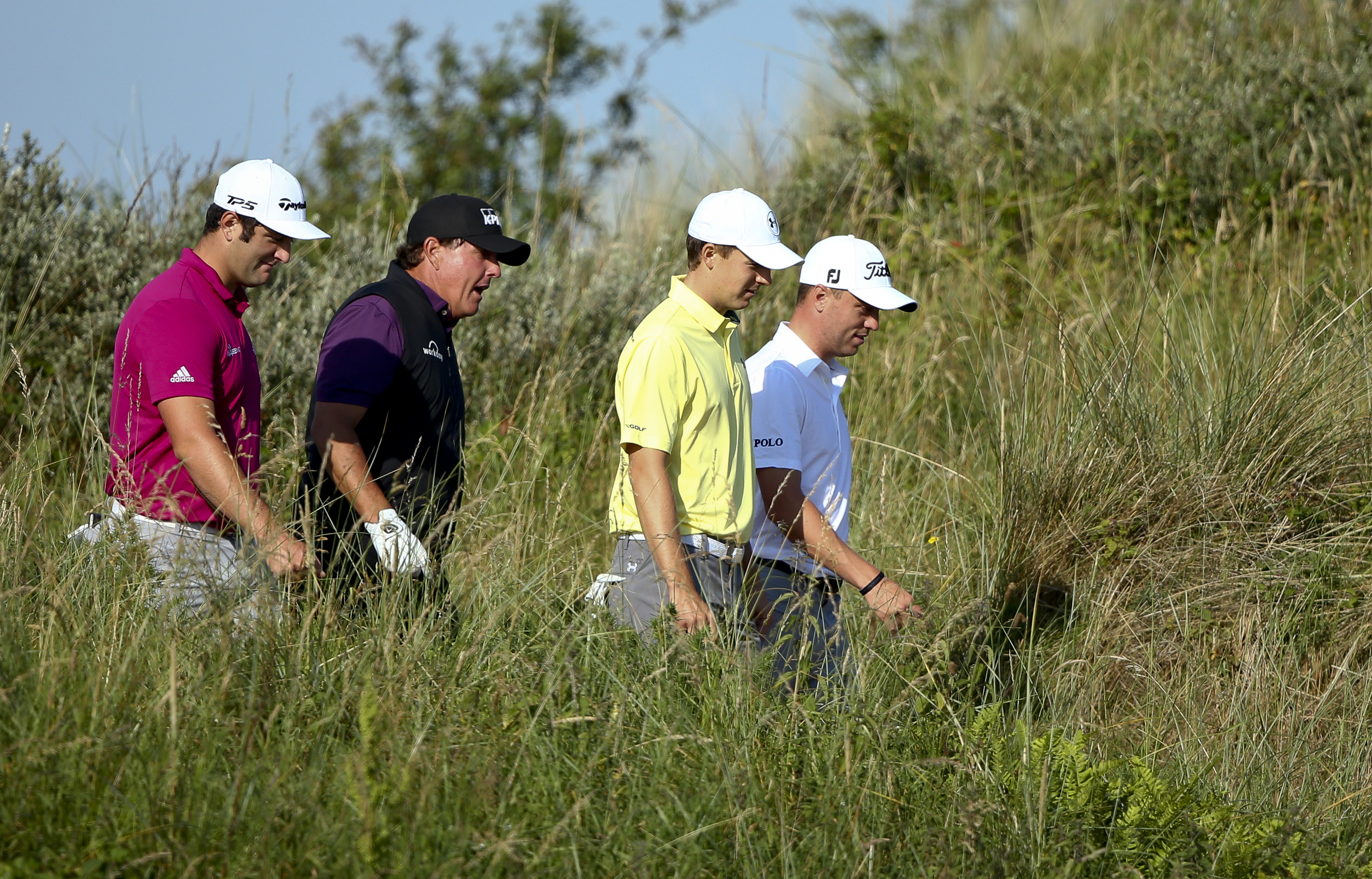 Spain's Jon Rahm, left with Phil Mickelson of the United States, Jordan Spieth of the United States and Justin Thomas of the United States talk together as they walk to the 3rd tee during a practice round ahead of the British Open Golf Championship, at Ro