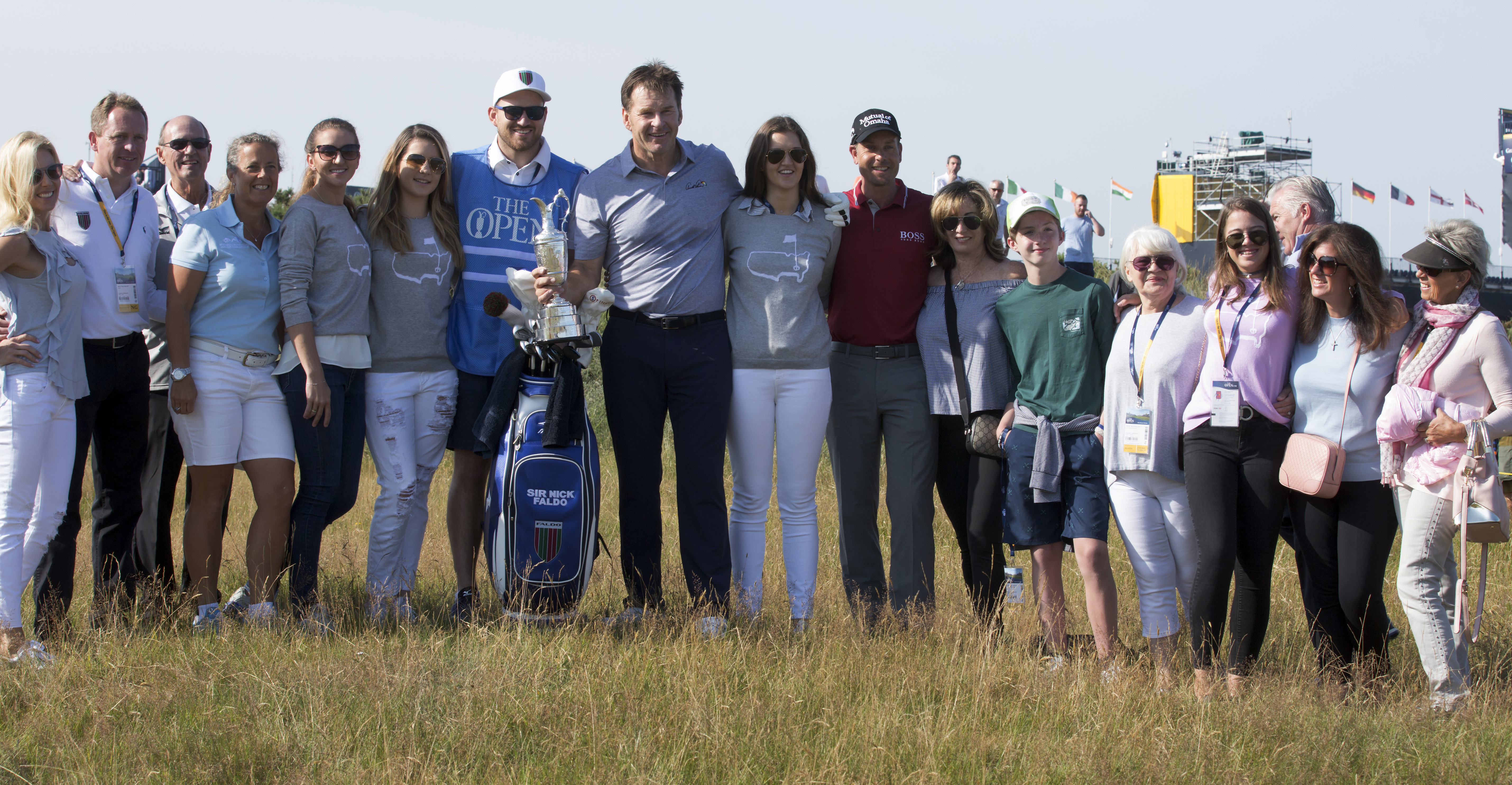 England's Nick Faldo, center, with Sweden's Henrik Stenson, center right, and family and friends pose near the 1st tee with the trophy prior to a practice round ahead of the British Open Golf Championship, at Royal Birkdale, Southport, England Tuesday, Ju