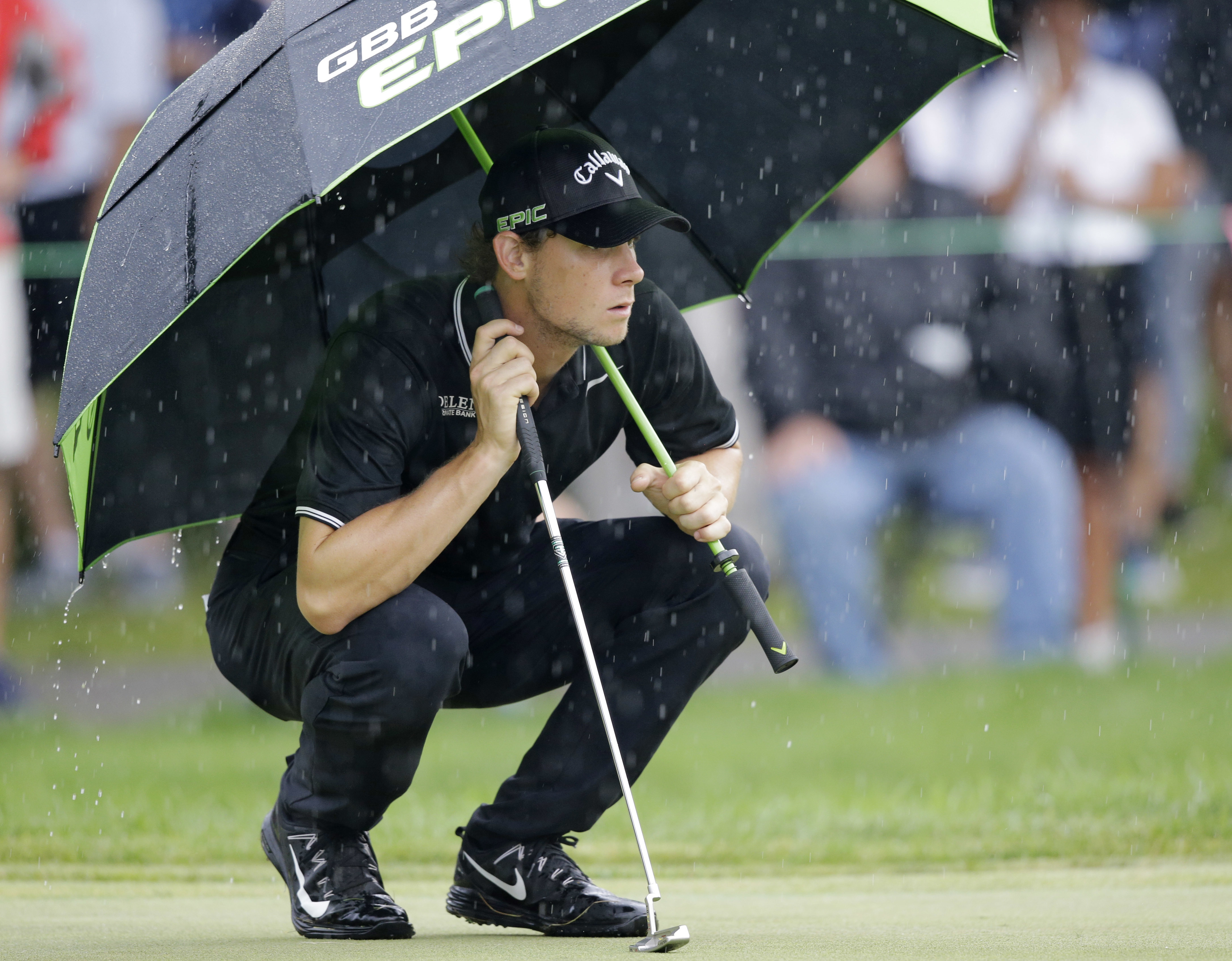 Thomas Pieters, from Belgium, waits to putt on the first green as rain falls during the second round of the Bridgestone Invitational golf tournament at Firestone Country Club, Friday, Aug. 4, 2017, in Akron, Ohio. (AP Photo/Tony Dejak)