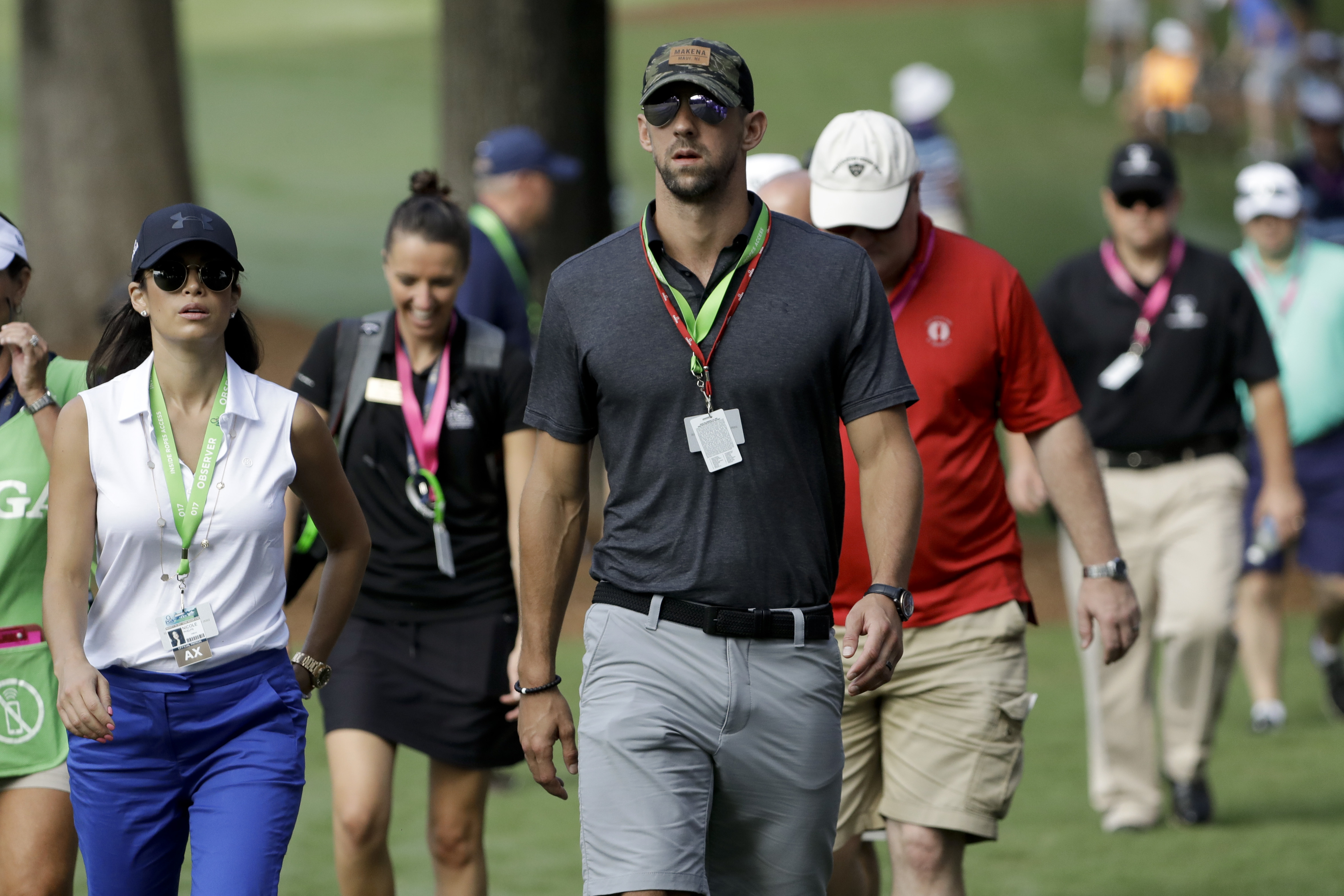 Swimmer, Michael Phelps walks the back ninth during the first round of the PGA Championship golf tournament at the Quail Hollow Club Thursday, Aug. 10, 2017, in Charlotte, N.C. (AP Photo/Chris O'Meara)