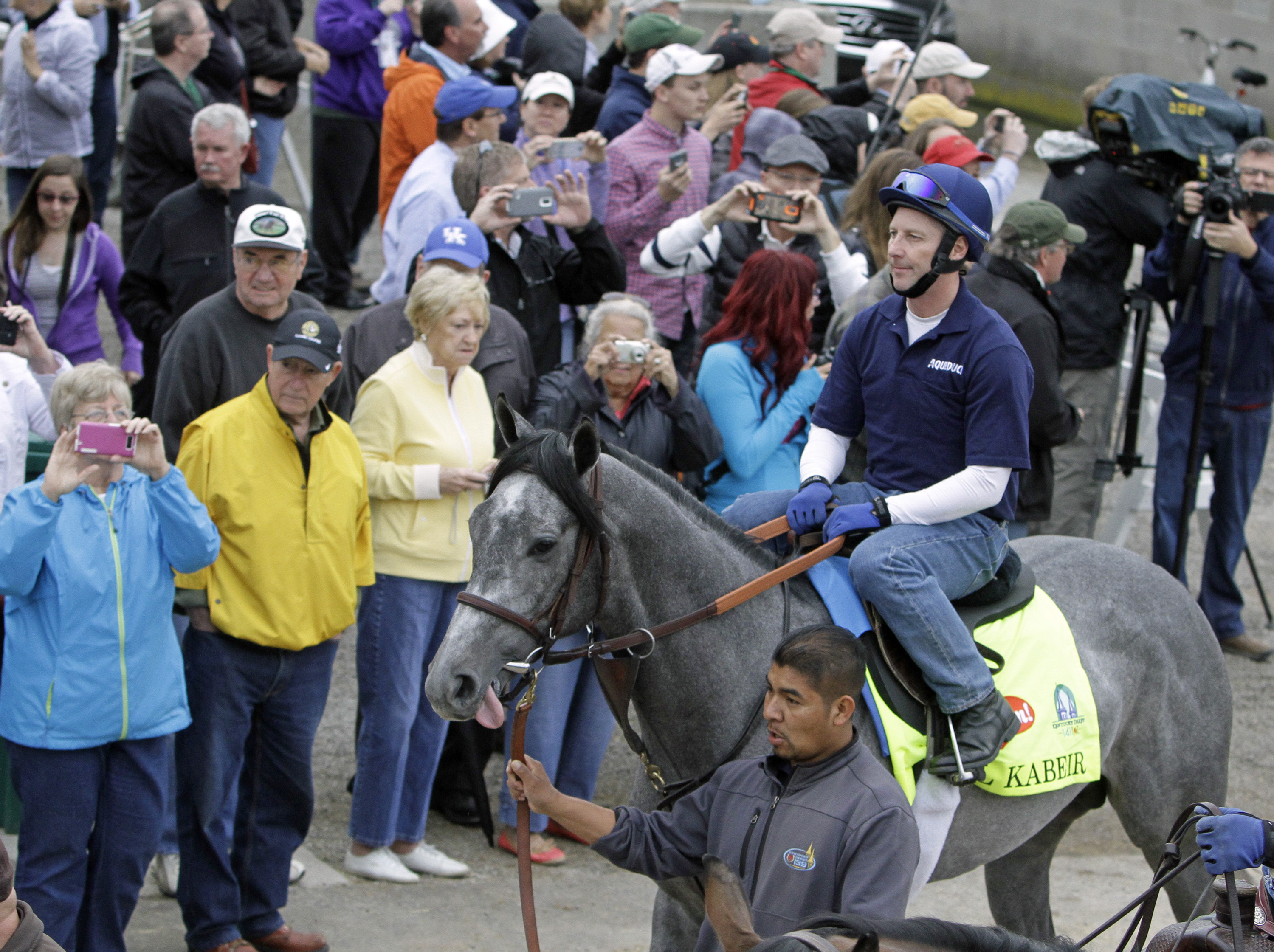 Kentucky Derby entrant El Kabeir, with exercise rider Simon Harris in the saddle, is led to the track through a crowd outside Barn 33 at Churchill Downs in Louisville, Ky., Thursday, April 30, 2015.  (AP Photo/Garry Jones)