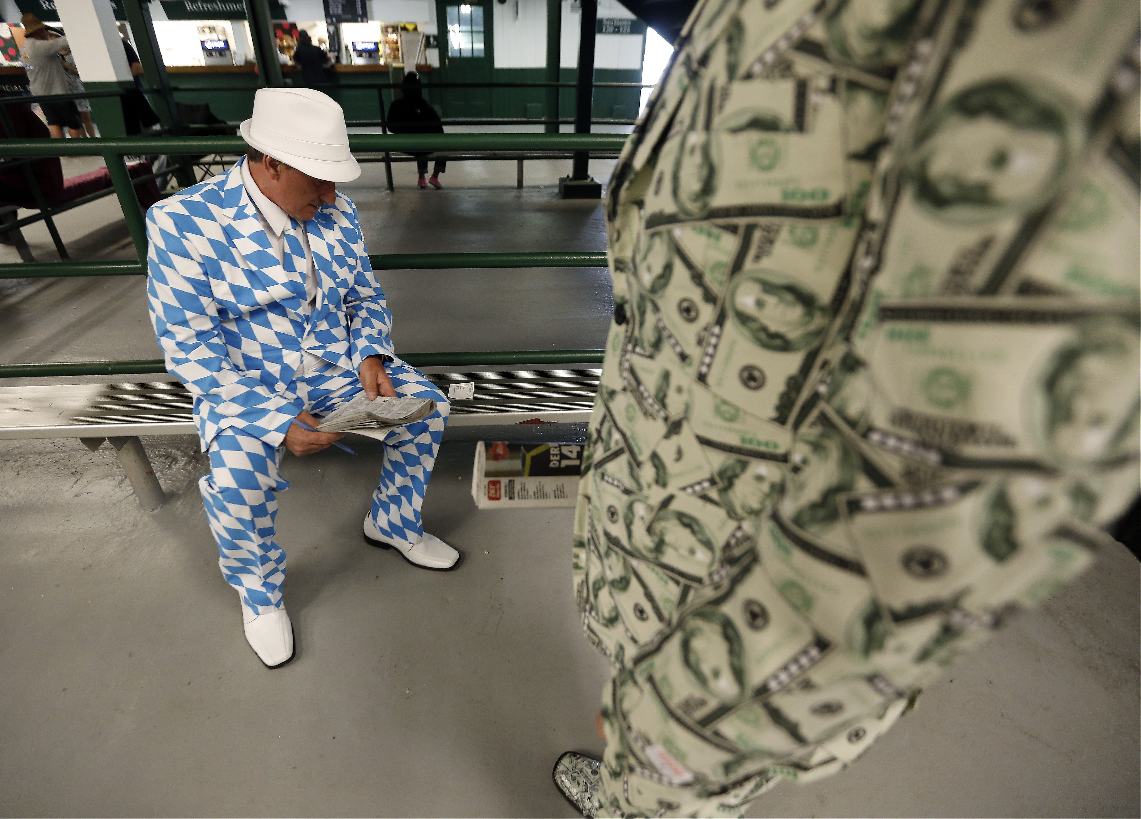 Michael Parrett, left, and Dustin Doerflinger look over their bets before the 141st running of the Kentucky Derby horse race at Churchill Downs Saturday, May 2, 2015, in Louisville, Ky. (AP Photo/Charlie Riedel)
