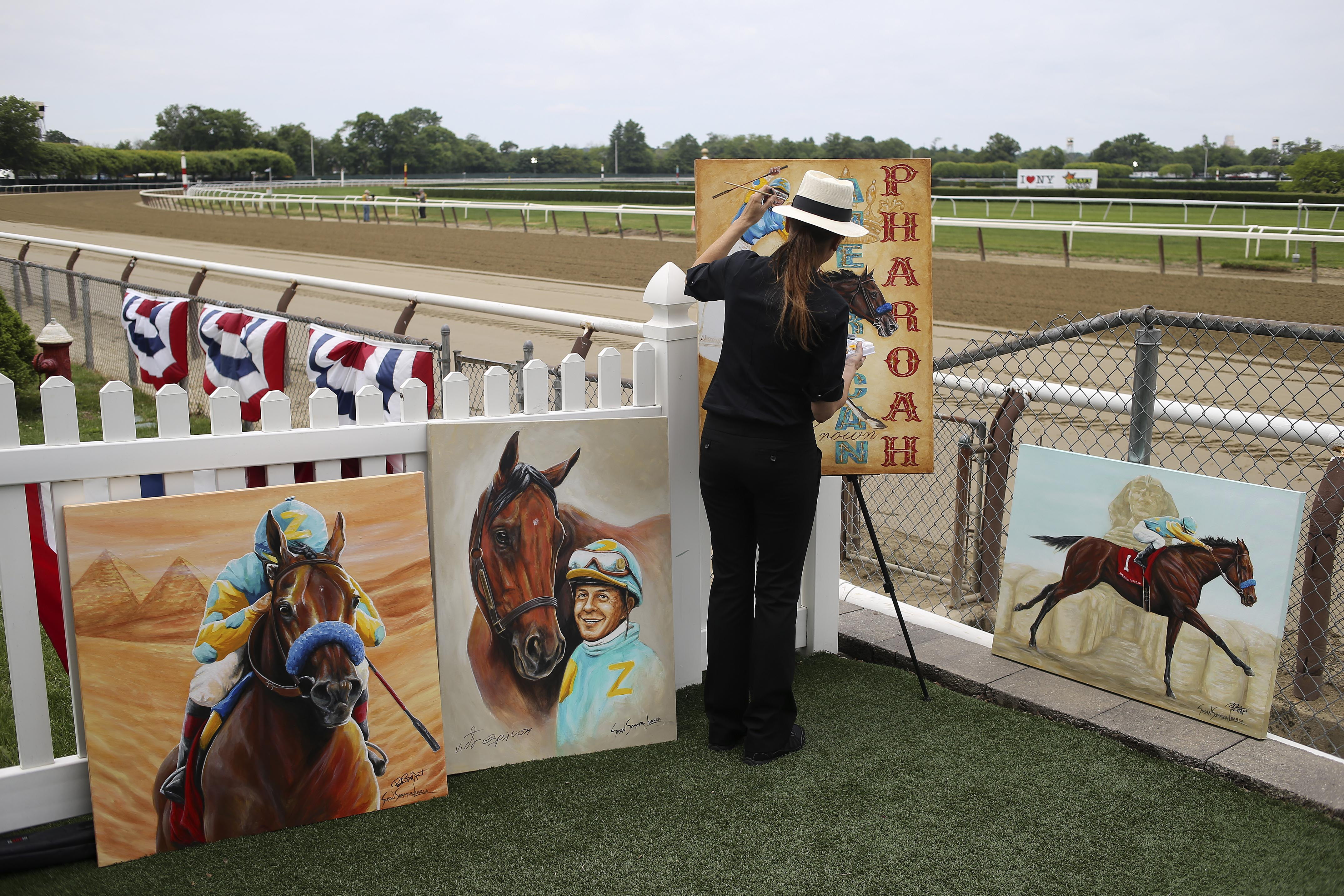 Painter Susan Sommer-Luarca paints a picture of American Pharoah before the 147th running of the Belmont Stakes horse race at Belmont Park, Saturday, June 6, 2015, in Elmont, N.Y. (AP Photo/Seth Wenig)