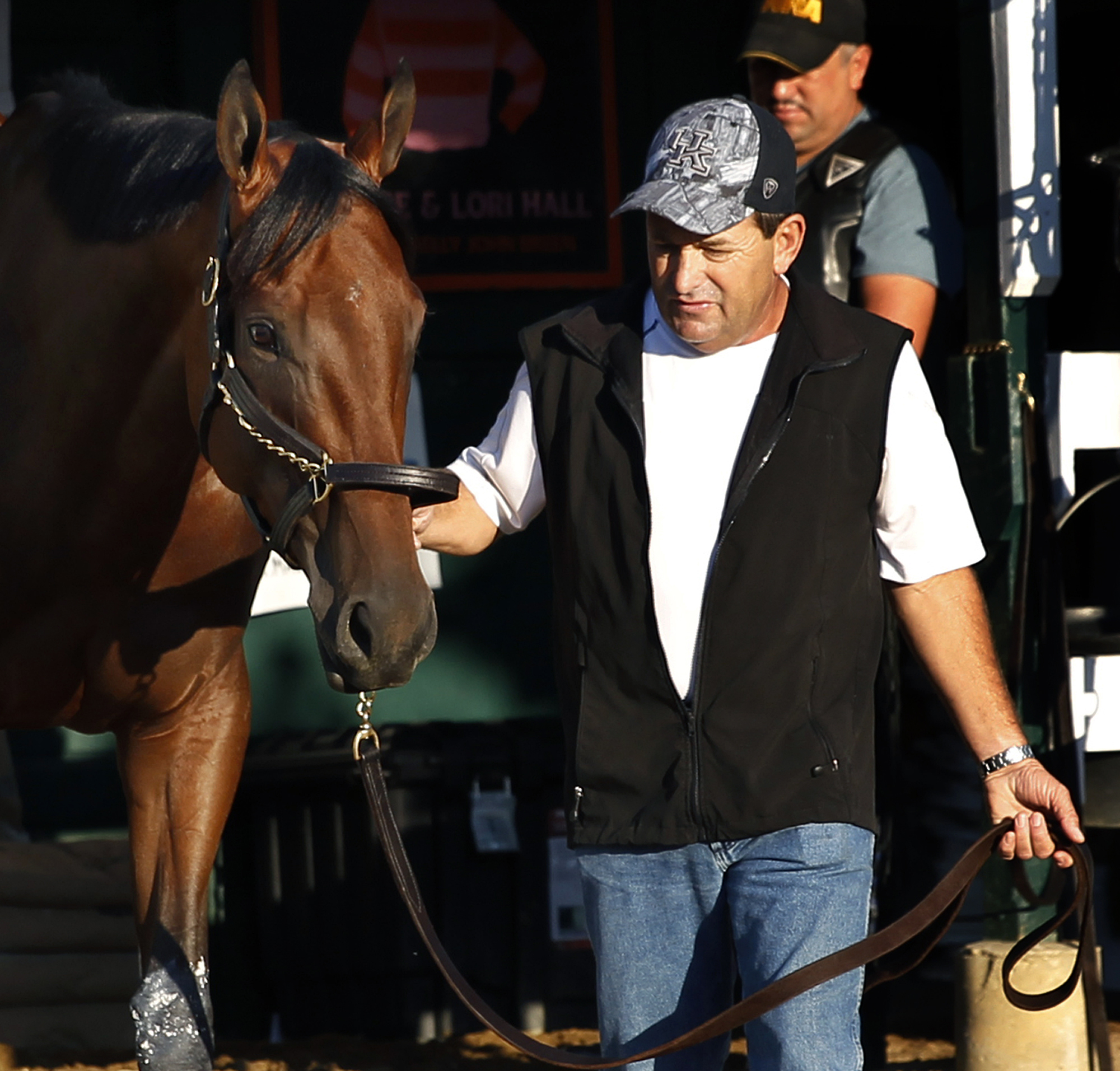 Assistant trainer Jimmy Barnes walks Triple Crown winner American Pharoah in the stable area at Monmouth Park in Oceanport, N.J., early Sunday, Aug. 2, 2015. American Pharoah is preparing for Sunday's running of the Haskell Invitational horse race. (AP Ph