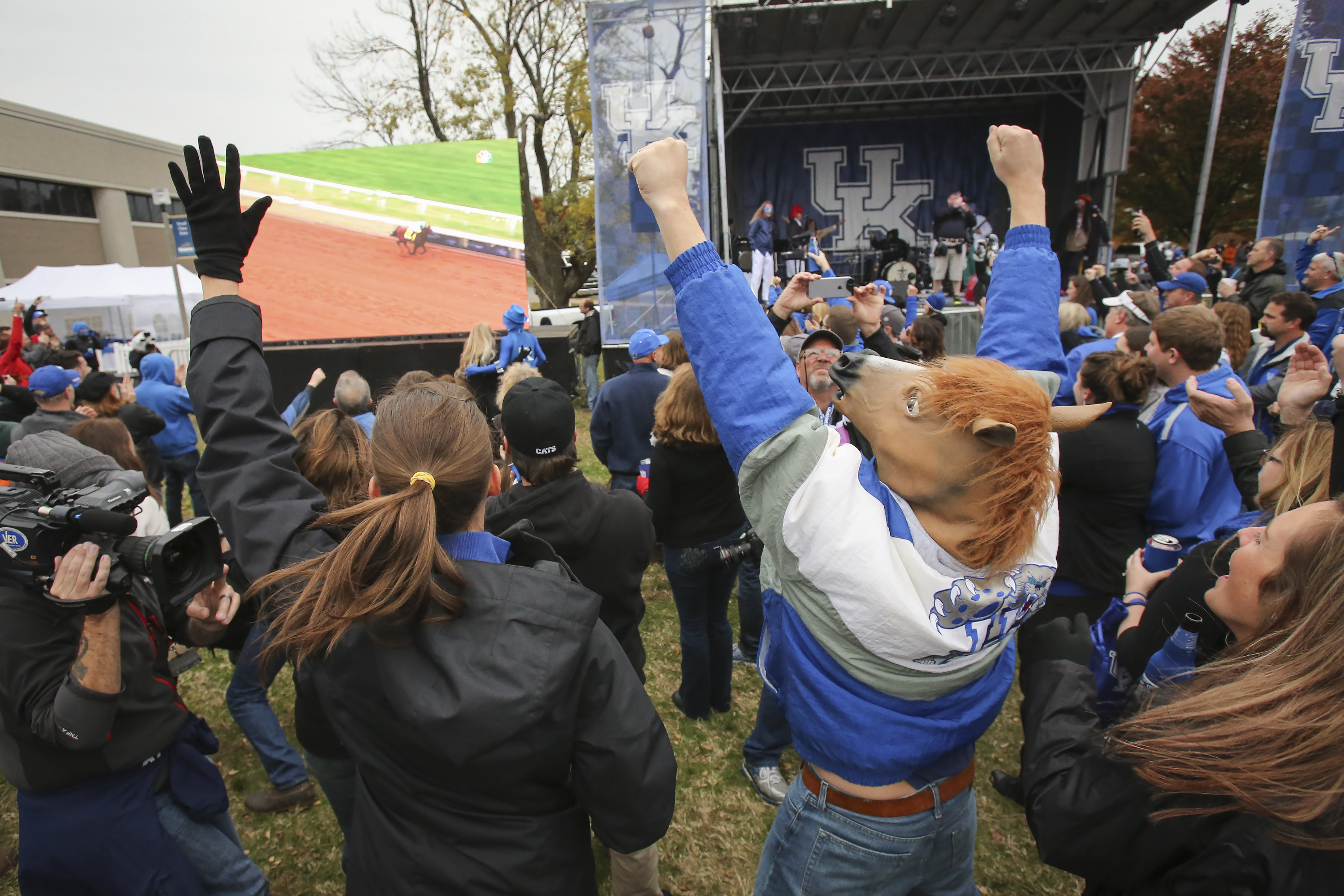Wearing a horse head mask, Chase Milner and his wife Rebecca cheer as they watch American Pharoah win the Breeders' Cup Classic in the parking lot of Commonwealth Stadium before Kentucky played Tennessee in an NCAA college football game Saturday, Oct. 31,