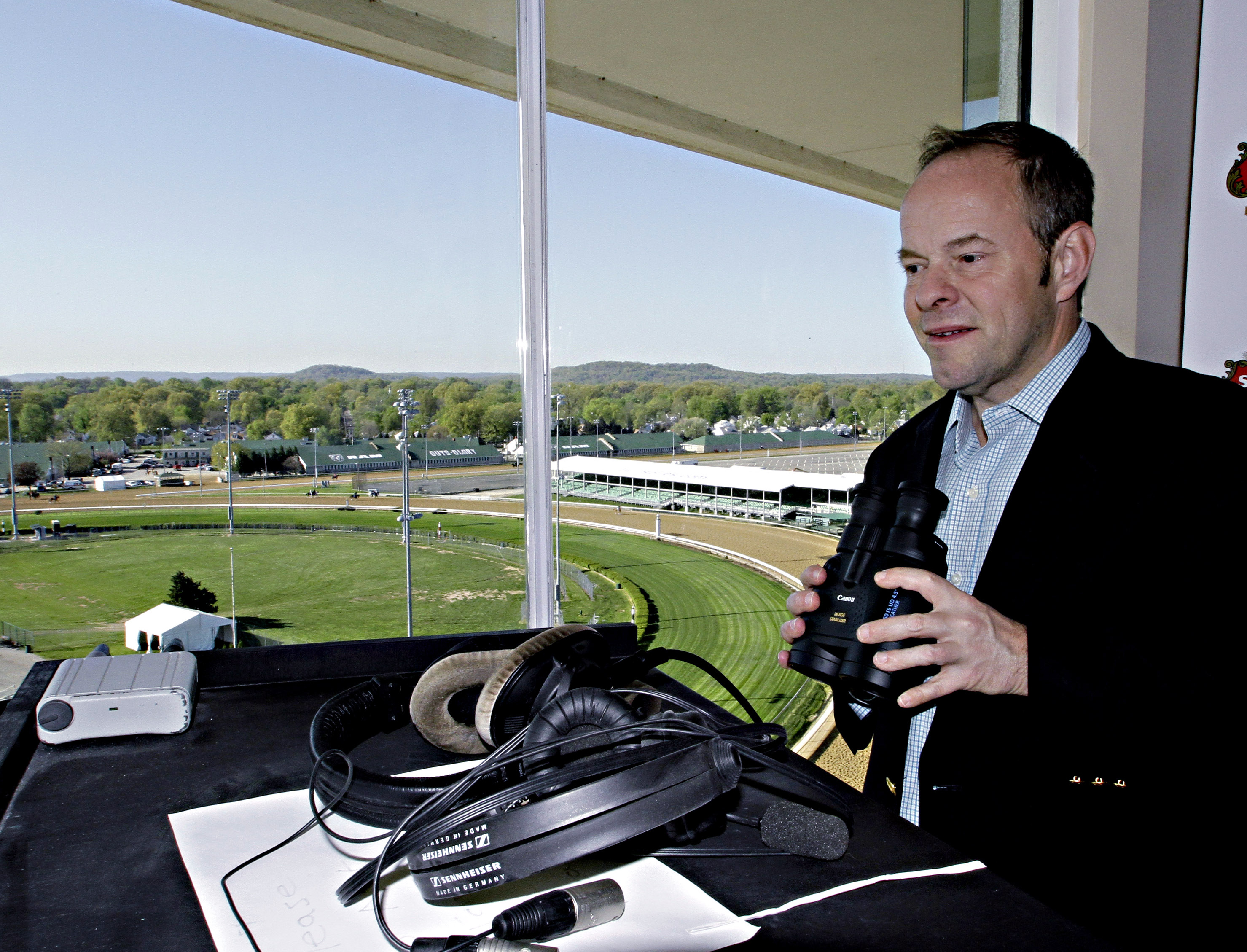 FILE - In this April 23, 2014 file photo, track announcer Larry Collmus looks out from his booth atop the grandstand at Churchill Downs in Louisville, Ky.  Collmus has signed a five-year contract extension with NBC Sports to remain the voice of the Triple