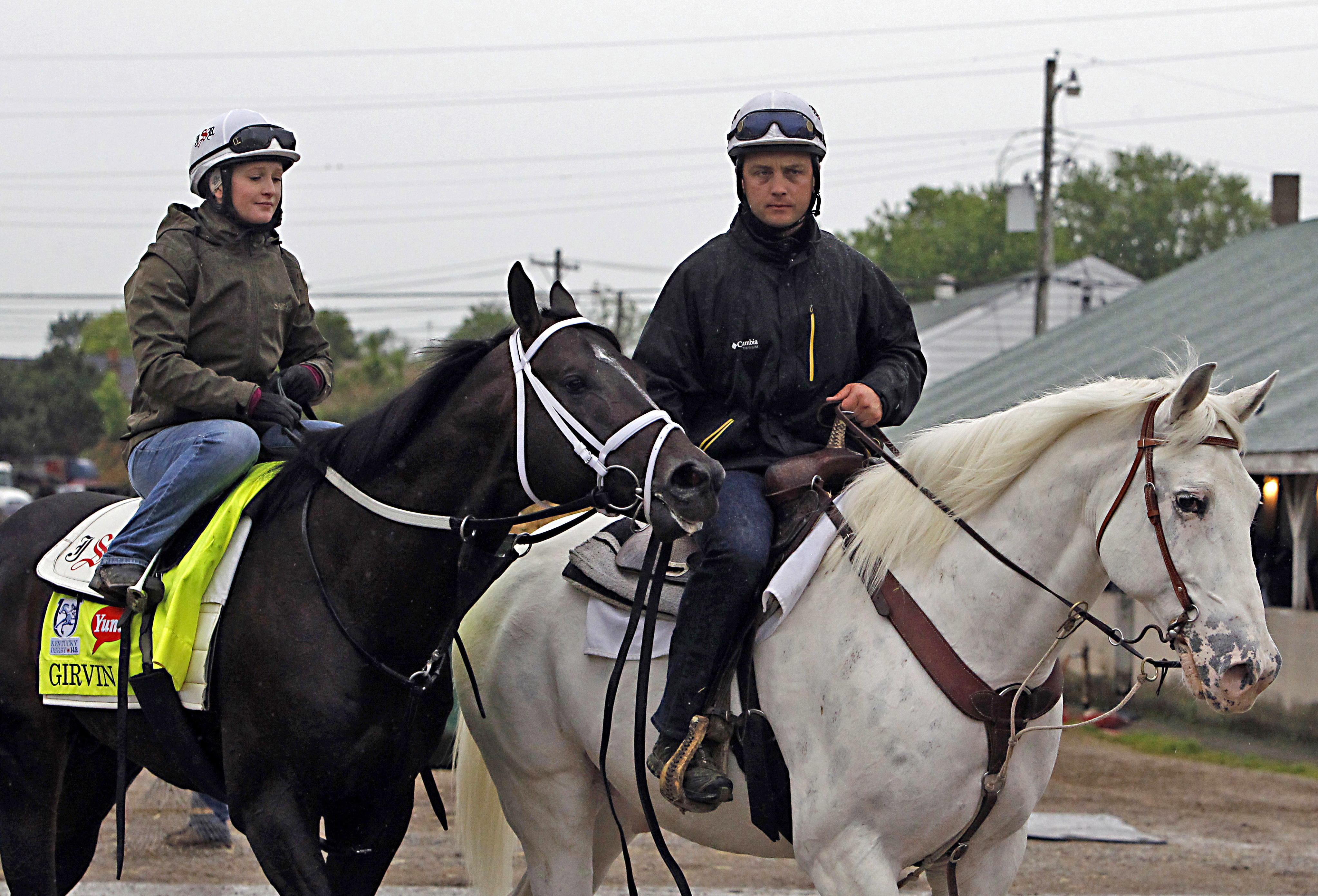Trainer Joe Sharp, right, leads Kentucky Derby entrant Girvin, left, ridden by his wife Rosie Napravnik, a former jockey, back to Barn 33 following a morning gallop at Churchill Downs in Louisville, Ky., Thursday, May 4, 2017. (AP Photo/Garry Jones)
