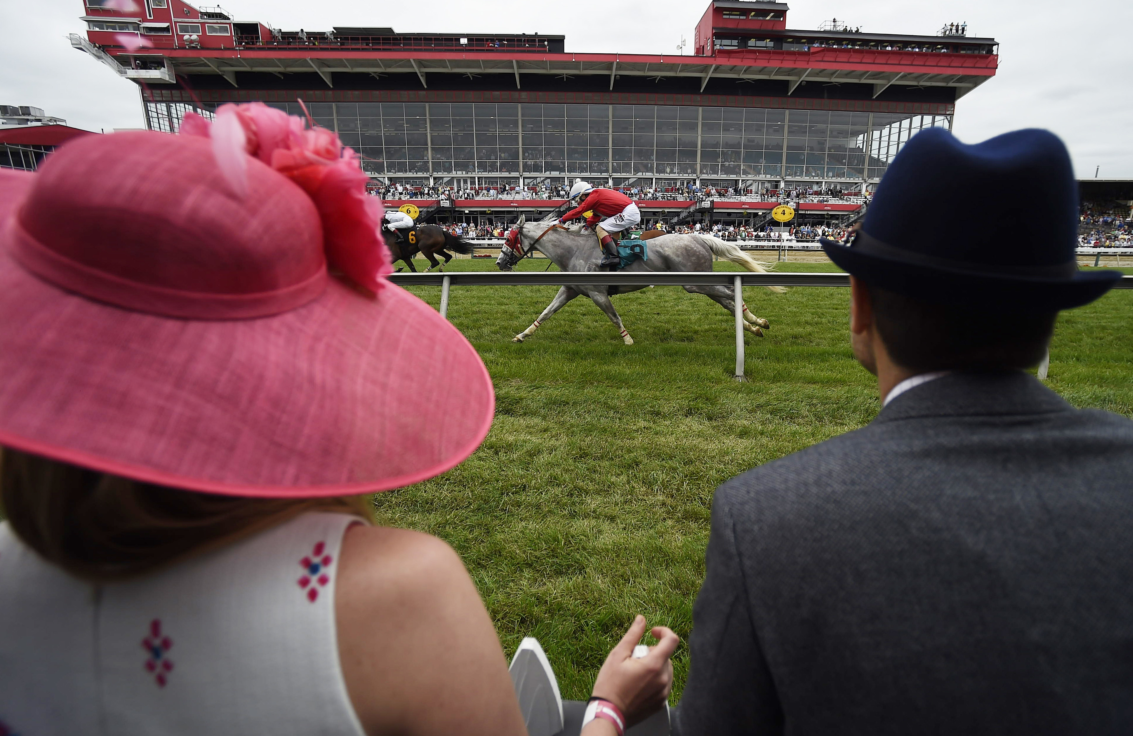 Katie Crammer and Zach Crammer of Maryland, watch the third race at the track ahead of the running of the Preakness Stakes horse race at Pimlico race course, Saturday, May 20, 2017, in Baltimore. The 142nd Preakness Stakes horse race runs Saturday. (AP Ph