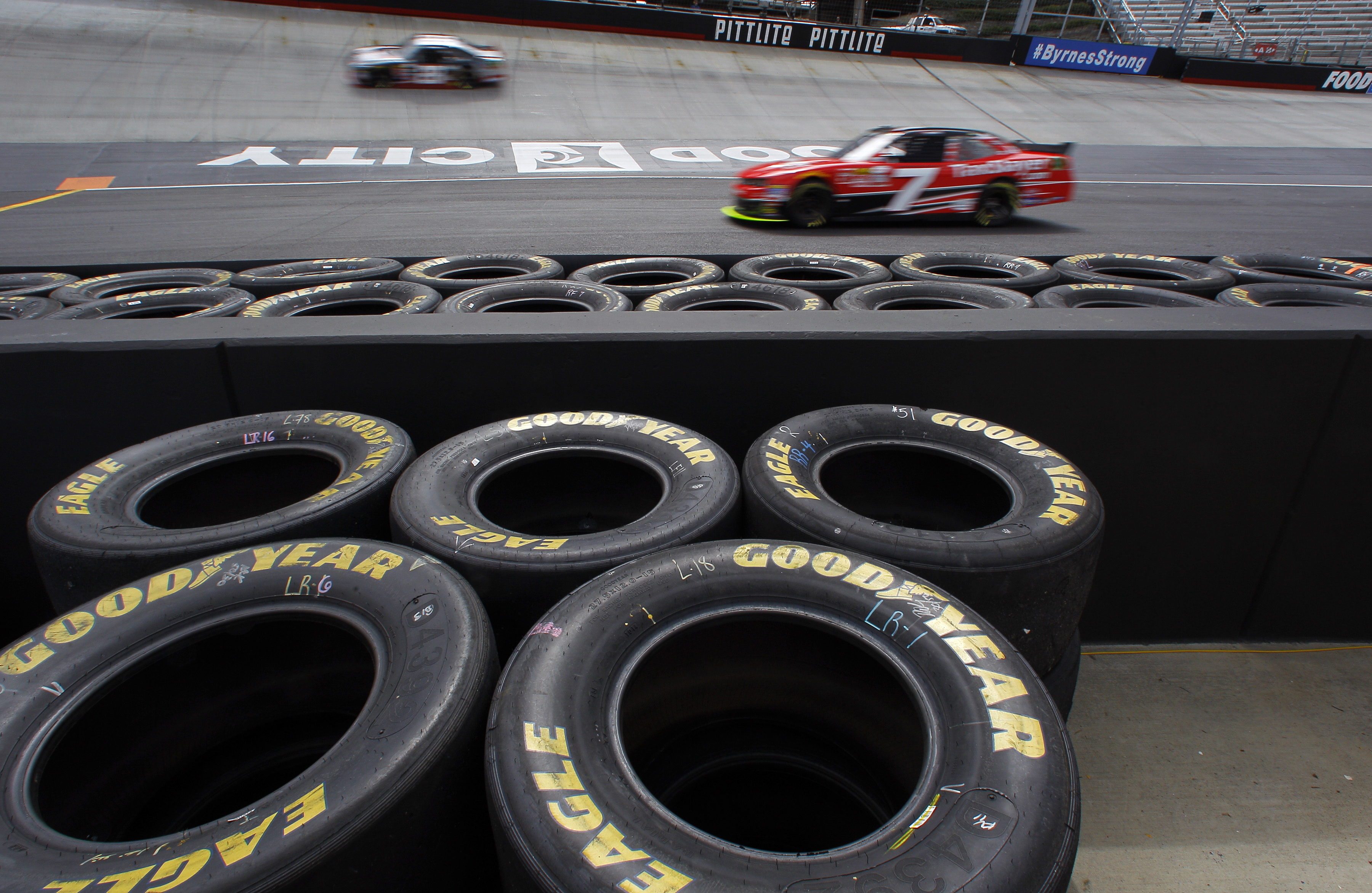 Driver Regan Smith (7) enters the track as another car passes during practice for a NASCAR Xfinity Series auto race at Bristol Motor Speedway on Friday, April 17, 2015, in Bristol, Tenn. (AP Photo/Wade Payne)