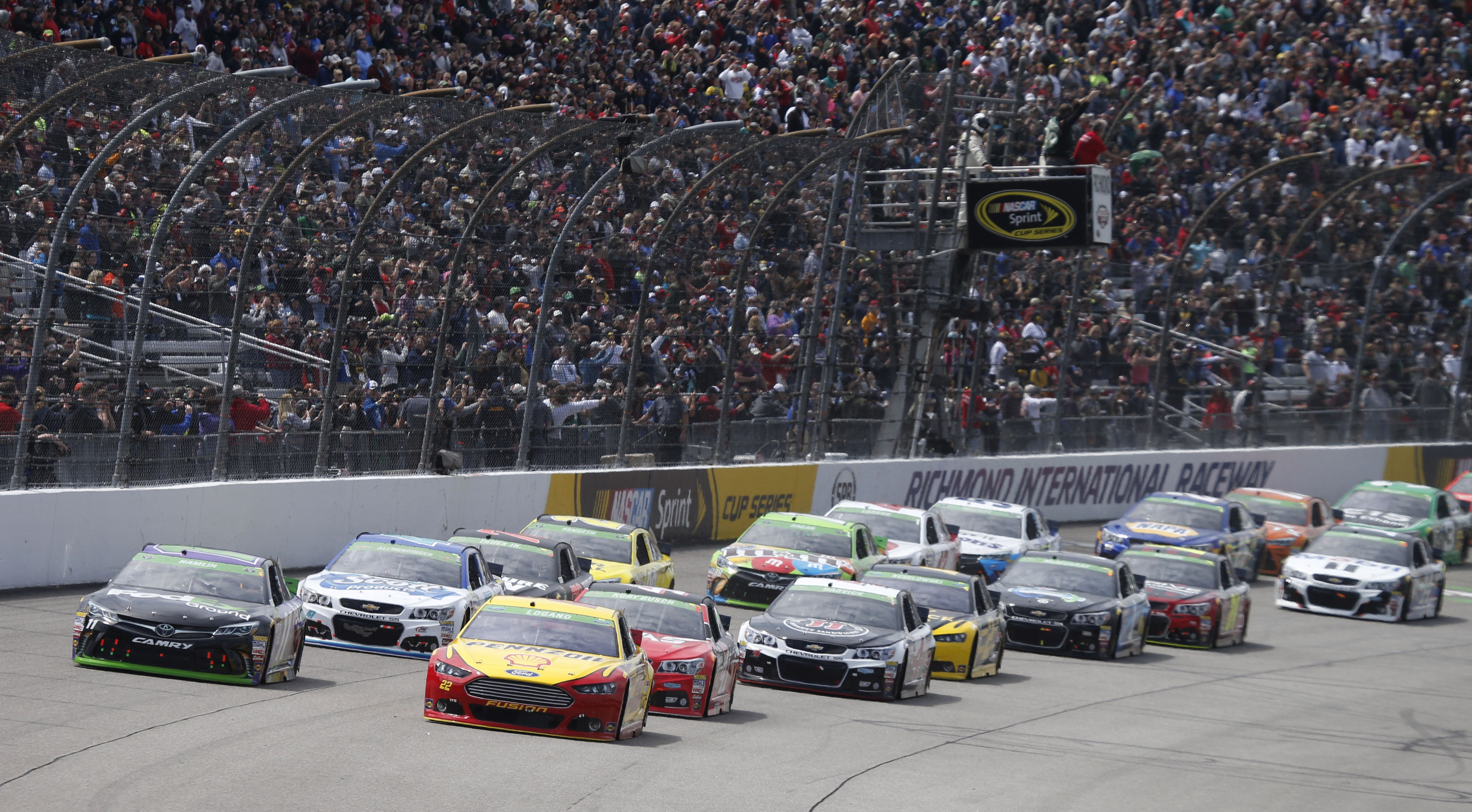 Joey Logano (22) and Denny Hamlin (11) lead the field at he start of the NASCAR Sprint Cup auto race at Richmond International Raceway in Richmond, Va., Sunday, April 26, 2015. (AP Photo/Steve Helber)