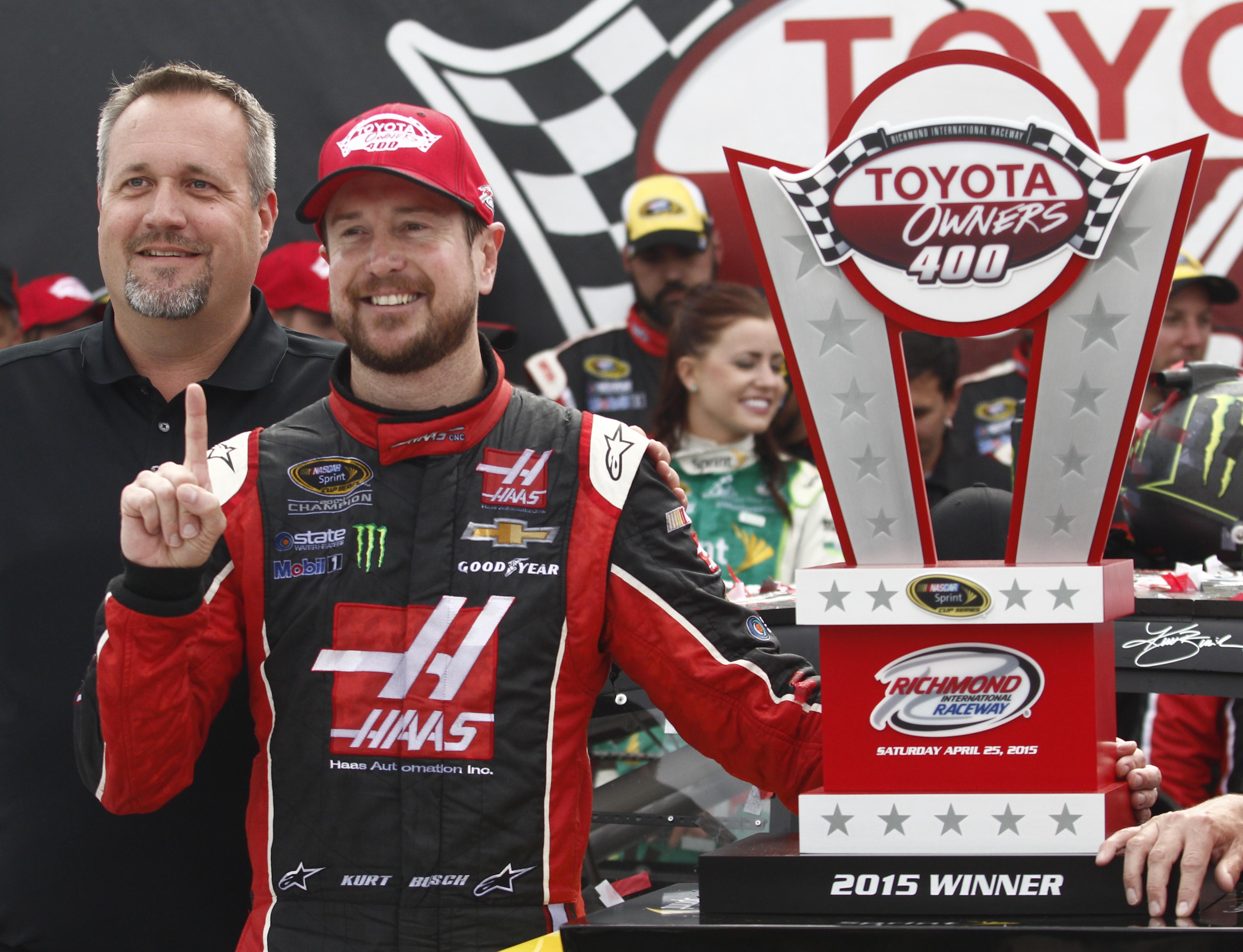 Kurt Busch, second from left, stands with the trophy after winning the NASCAR Sprint Cup auto race at Richmond International Raceway in Richmond, Va., Sunday, April 26, 2015. (AP Photo/Scott P. Yates)