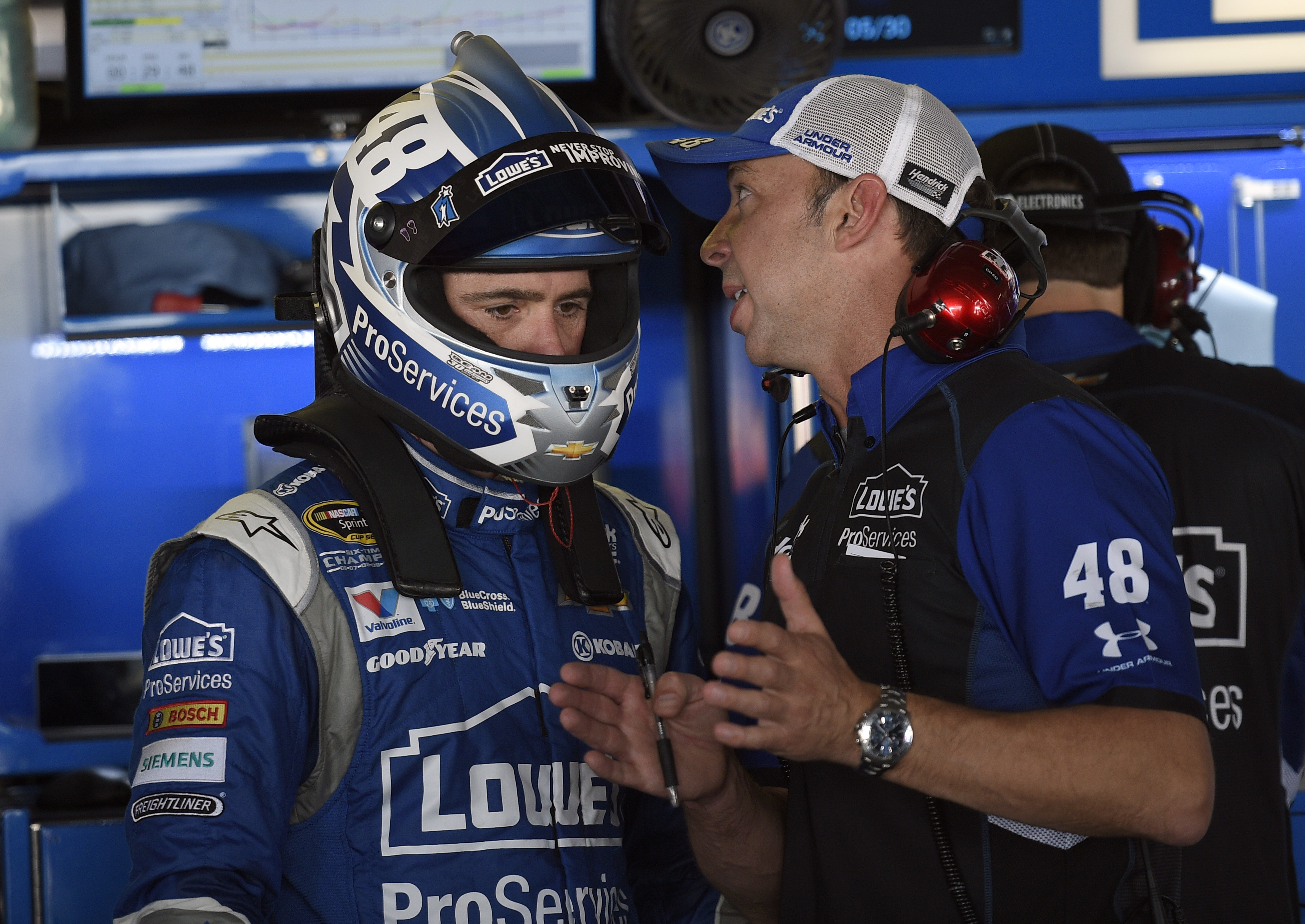 Jimmie Johnson, left, listens to his crew chief Chad Knaus, right, during practice for Sunday's NASCAR Sprint Cup series auto race, Saturday, May 30, 2015, at Dover International Speedway in Dover, Del. (AP Photo/Nick Wass)