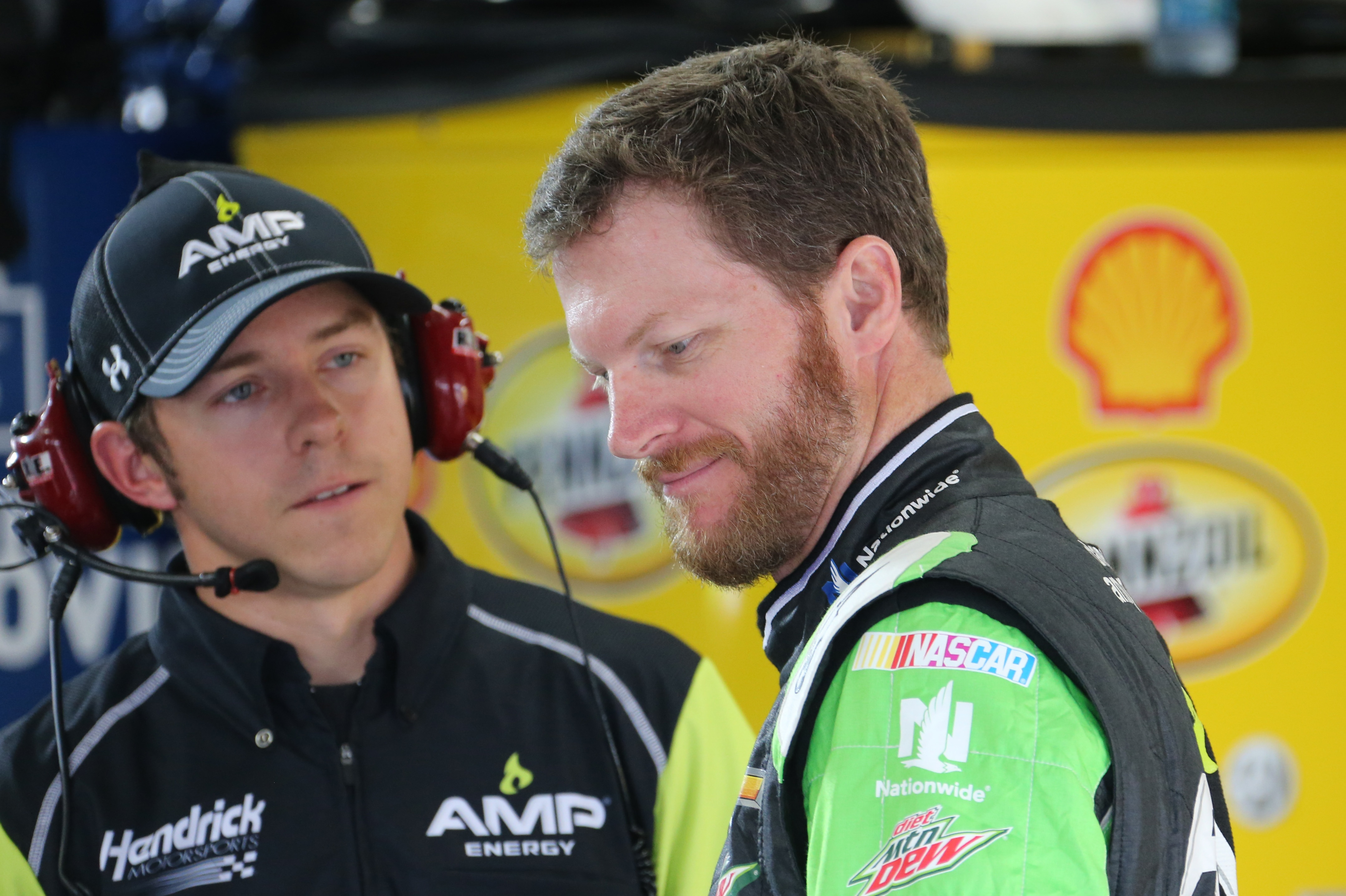 Dale Earnhardt Jr., right, talks with crew chief Greg Ives after practicing for Sunday's NASCAR Sprint Cup series auto race at Michigan International Speedway, Friday, June 12, 2015, in Brooklyn, Mich. (AP Photo/Bob Brodbeck)