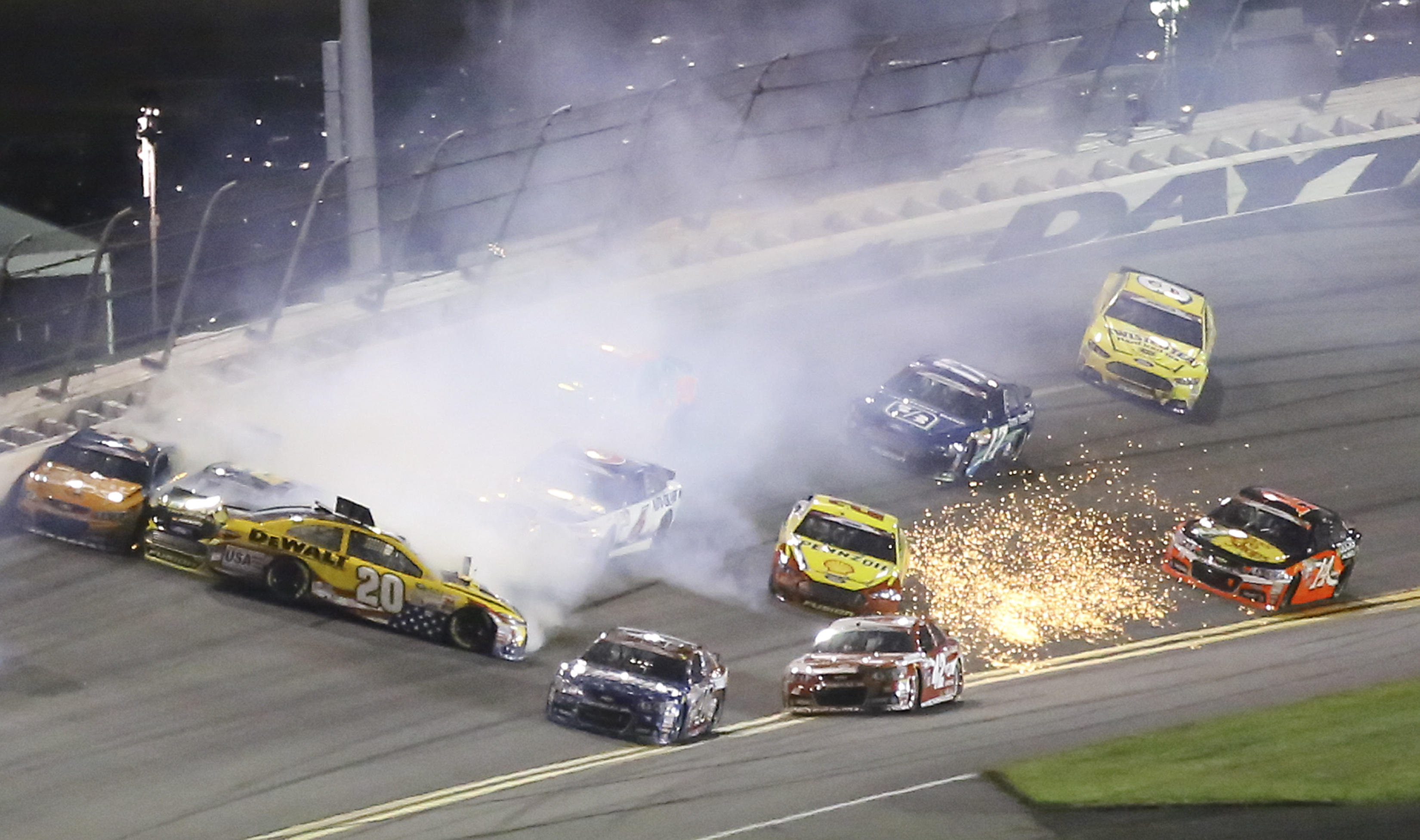 Matt Kenseth (20) gets turned sideways as he is involved in a multi-car crash including Kevin Harvick (4) and Joey Logano (22) coming out of turn 4 during a NASCAR Sprint Cup series auto race at Daytona International Speedway, Monday, July 6, 2015, in Day
