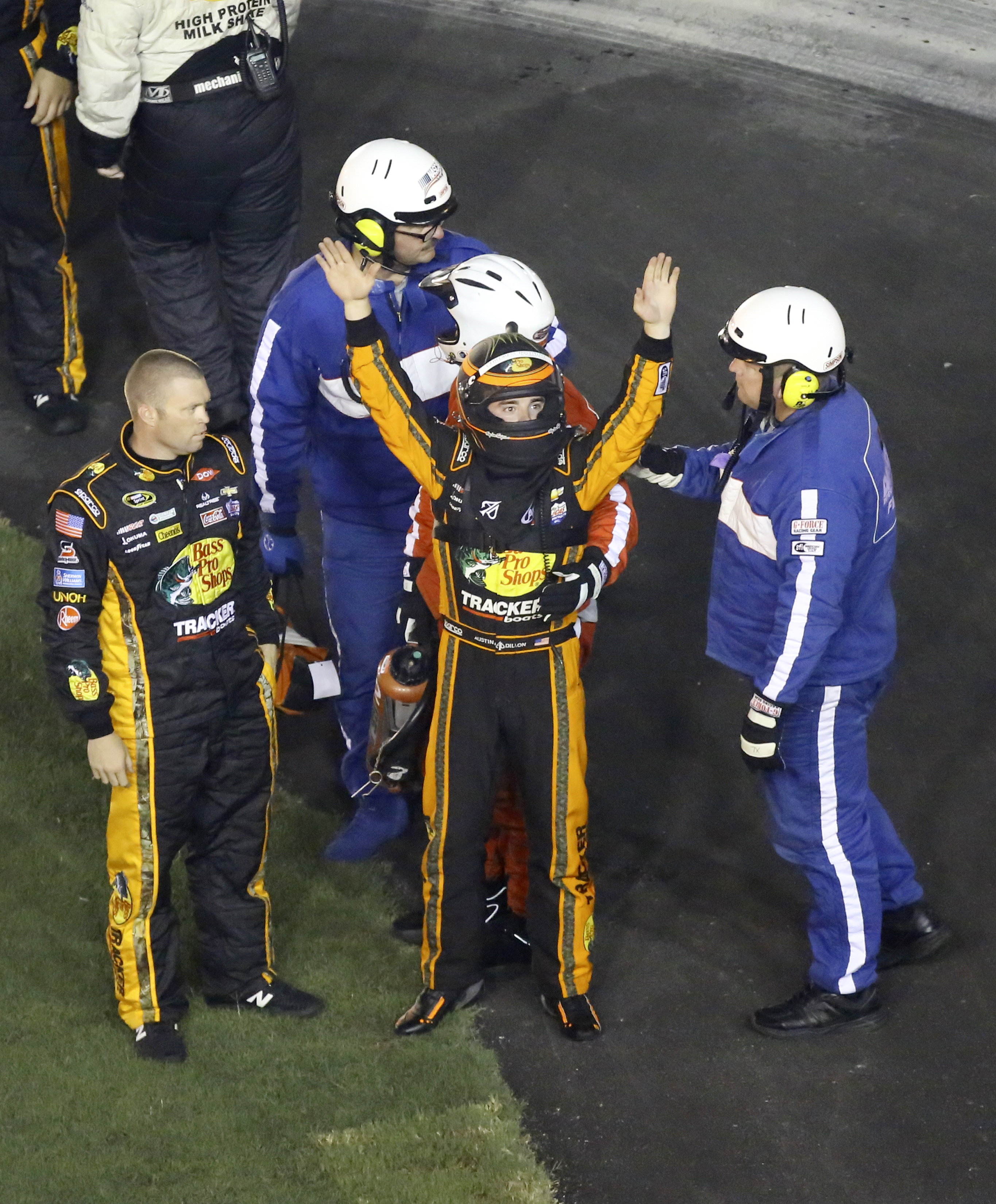 Austin Dillon, center, raises his arms to race fans to signify he was okay after he was involved in a multi-car crash in a NASCAR Sprint Cup series auto race at Daytona International Speedway, Monday, July 6, 2015, in Daytona Beach, Fla. (AP Photo/David G