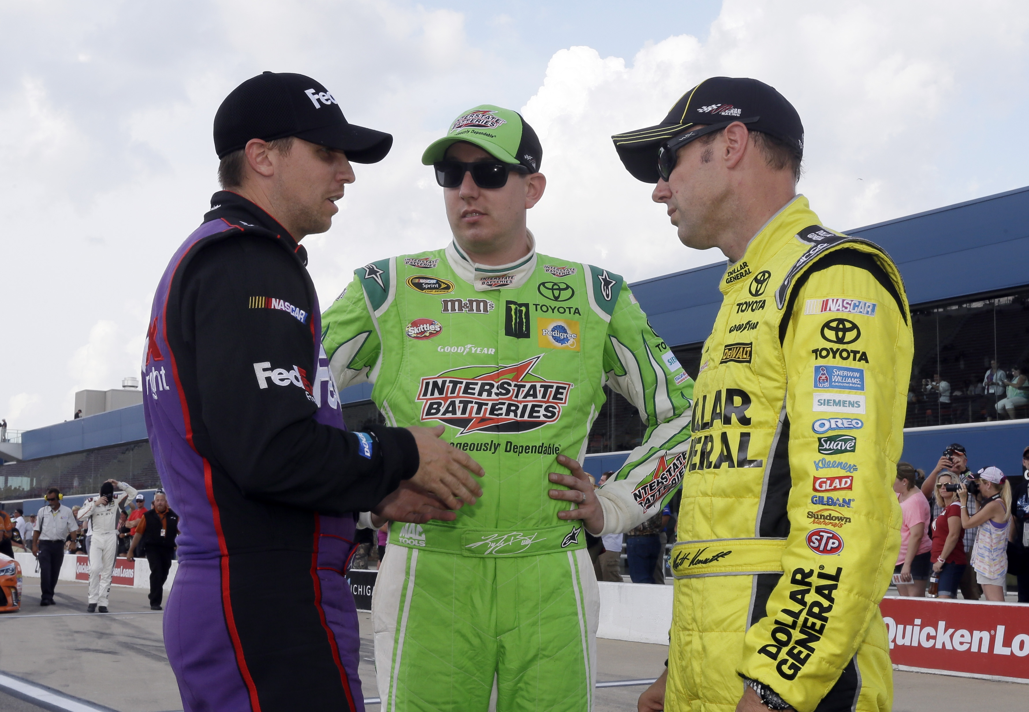 Denny Hamlin, left, talks with Kyle Busch, center, and Matt Kenseth after qualifying Friday, Aug. 14, 2015, for the NASCAR Sprint Cup series auto race at Michigan International Speedway,in Brooklyn, Mich. Kenseth won the pole. (AP Photo/Carlos Osorio)