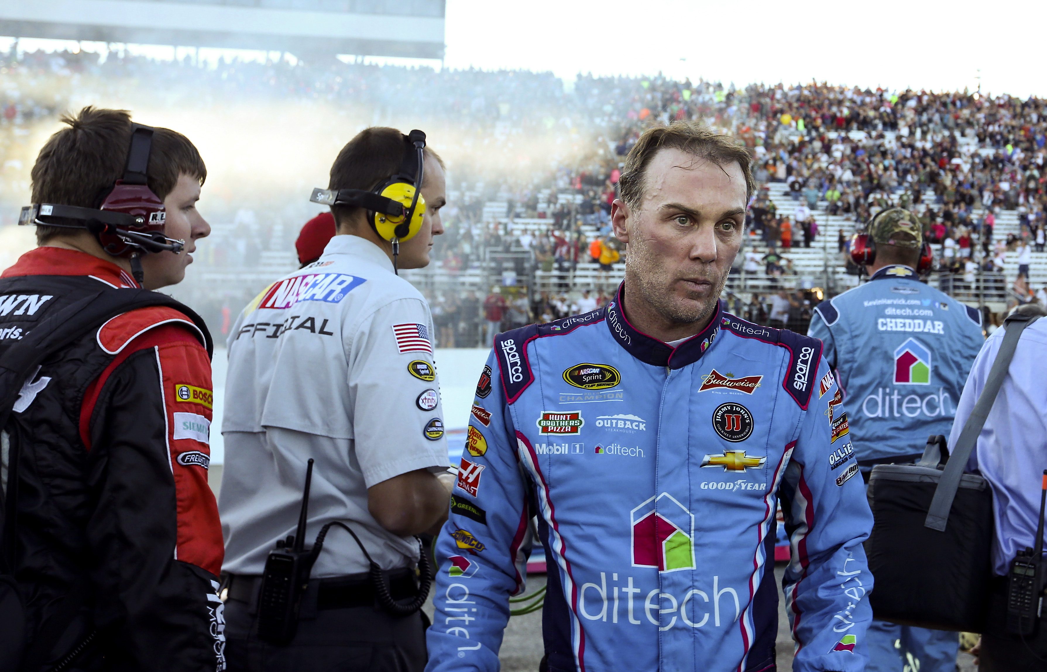 Smoke from Matt Kenseth's victory burnout hangs in the air behind Kevin Harvick as Harvick leaves the pit area after the NASCAR Sprint Cup series auto race at New Hampshire Motor Speedway in Loudon, N.H., Sunday, Sept. 27, 2015. Harvick, who was in the le