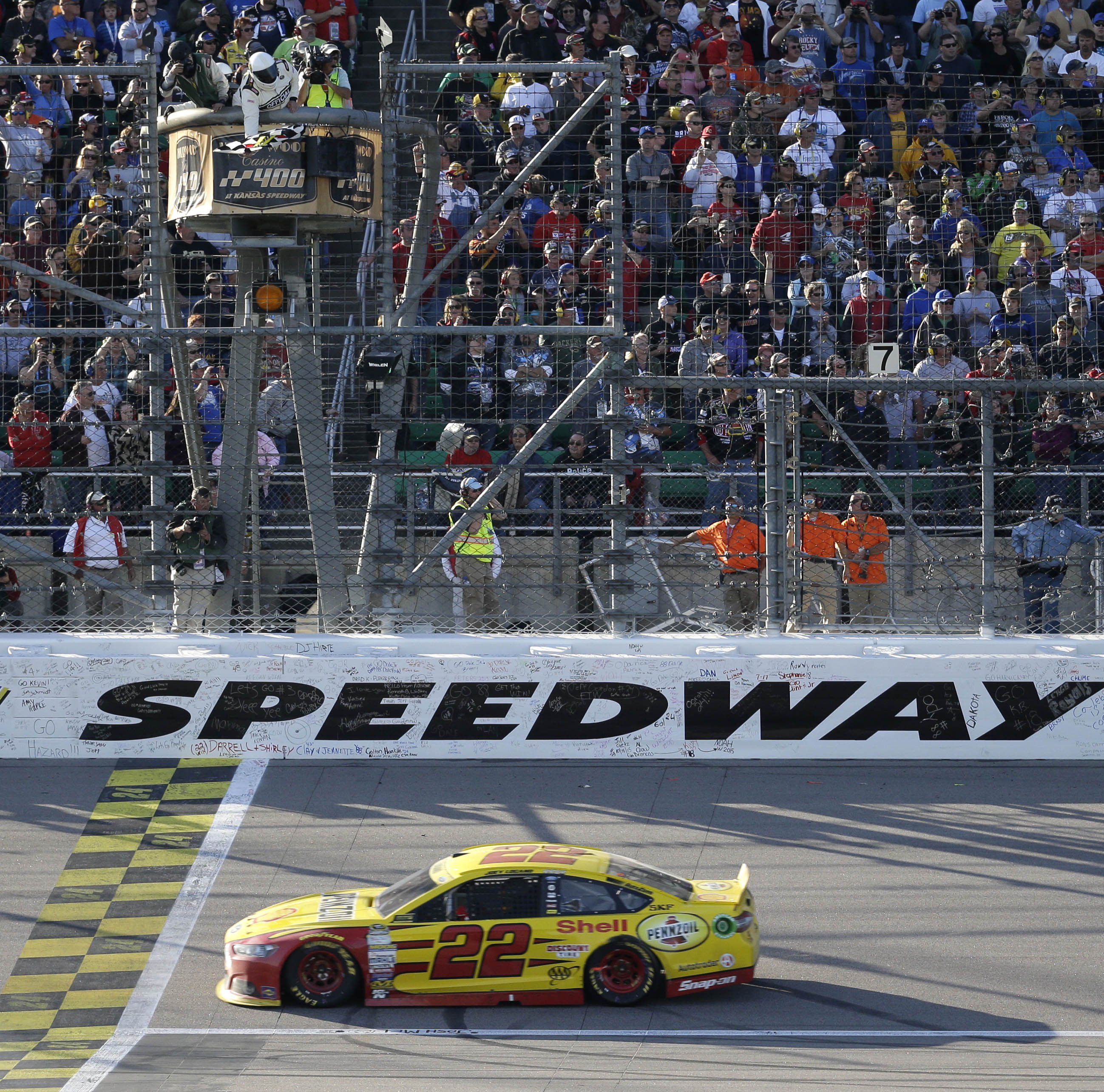 Sprint Cup Series driver Joey Logano (22) takes the checkered flag to win a NASCAR auto race at Kansas Speedway in Kansas City, Kan., Sunday, Oct. 18, 2015. (AP Photo/Orlin Wagner)