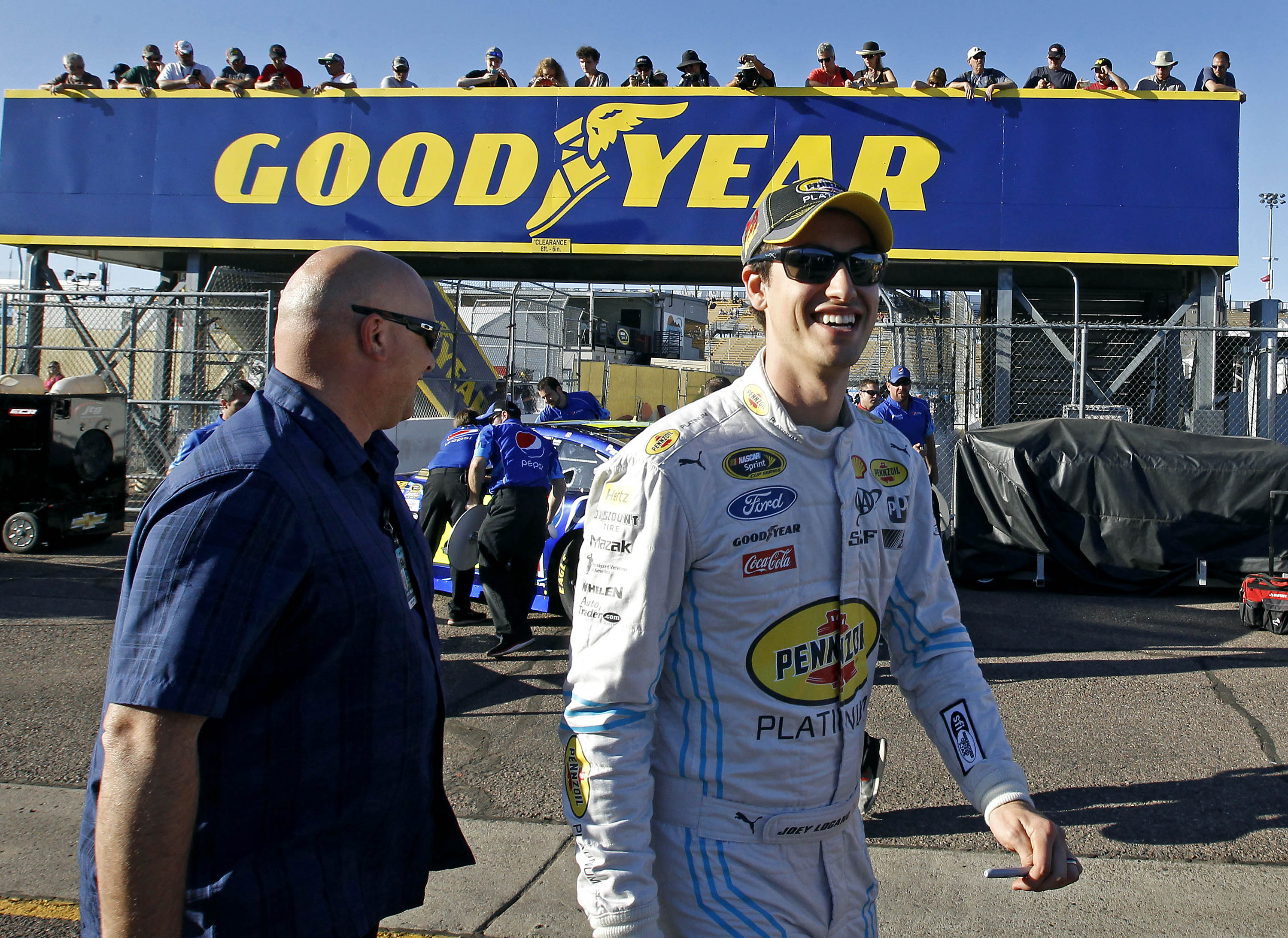 Joey Logano walks through the garage area before qualifying for Sunday's NASCAR Sprint Cup series auto race at Phoenix International Raceway, Friday, Nov. 13, 2015, in Avondale, Ariz. Logano is is looking to clinch a spot in the Chase for the Cup champion