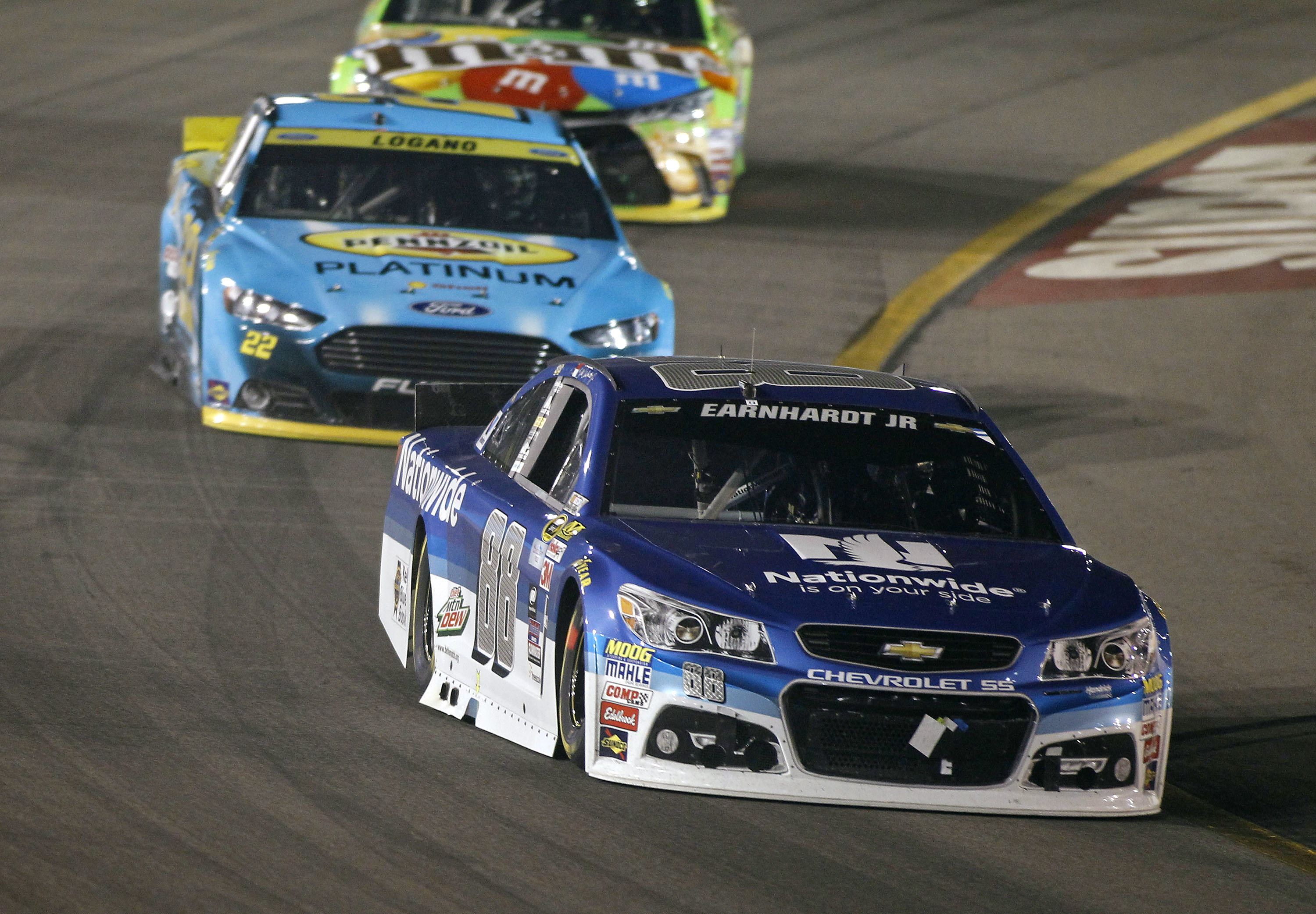 Dale Earnhardt Jr.(88) drives out of Turn 4 ahead of Joey Logano (22) and Kyle Busch during the NASCAR Sprint Cup series auto race at Phoenix International Raceway, Sunday, Nov. 15, 2015, in Avondale, Ariz. (AP Photo/Ralph Freso)