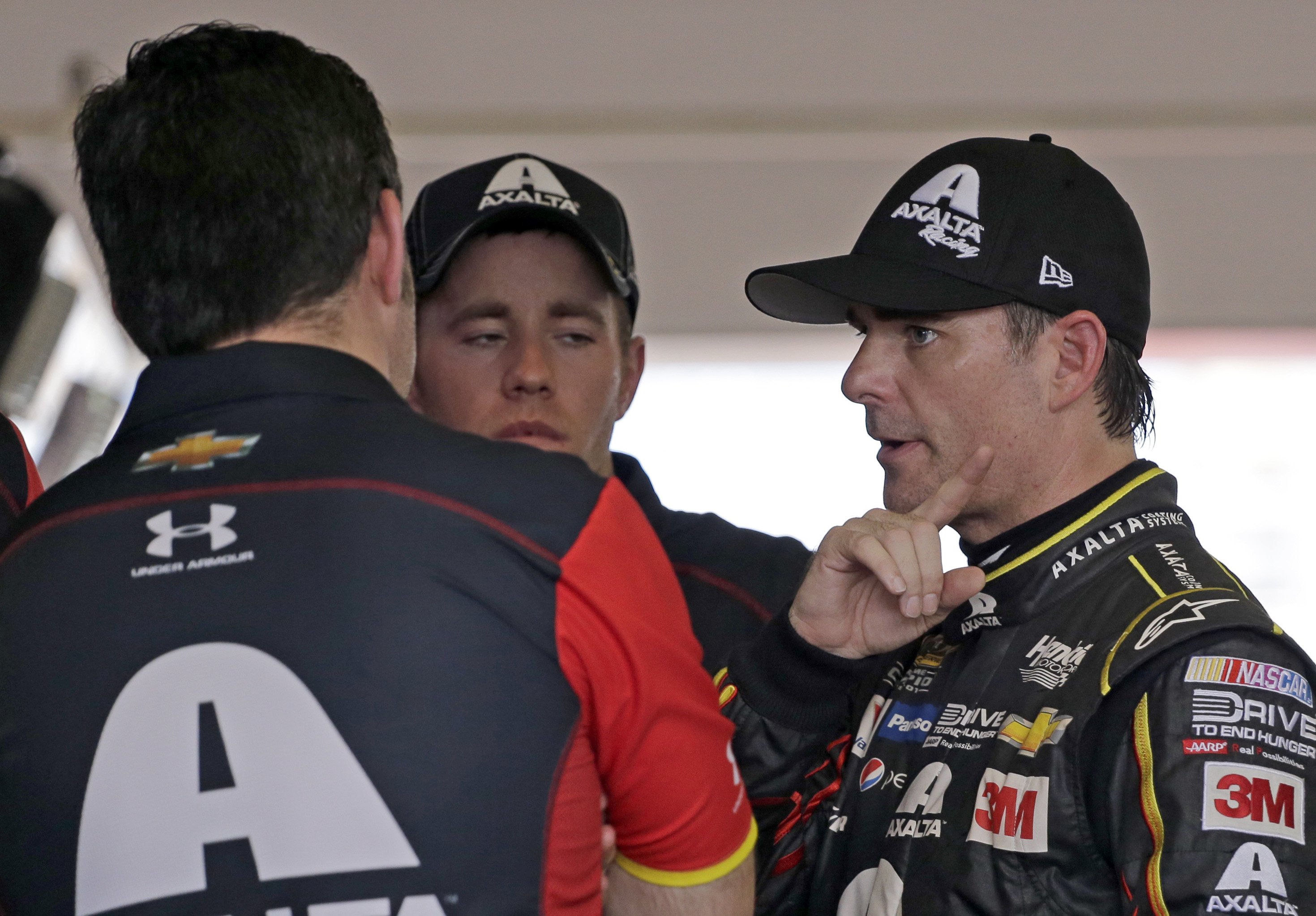 Jeff Gordon, right, talks to crew members after practice for Sunday's NASCAR Sprint Cup Series auto race, Saturday, Nov. 21, 2015, at Homestead-Miami Speedway in Homestead, Fla. (AP Photo/Terry Renna)