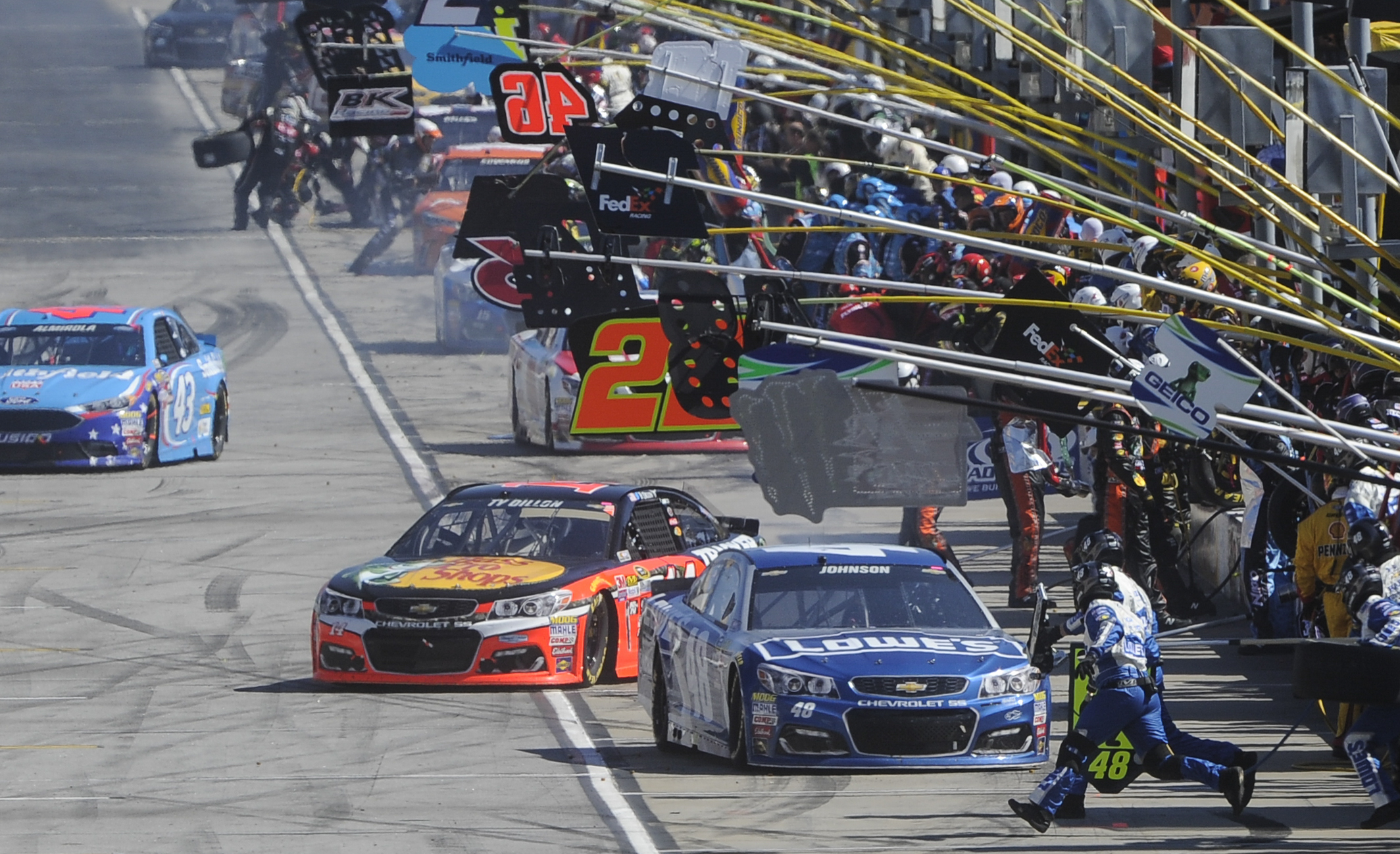 Jimmie Johnson,front  right, comes into the pit, as Ty Dillon pulls out behind during a NASCAR Sprint Cup Series auto race at Atlanta Motor Speedway, Sunday, Feb. 28, 2016, in Hampton, Ga. (AP Photo/John Amis\)