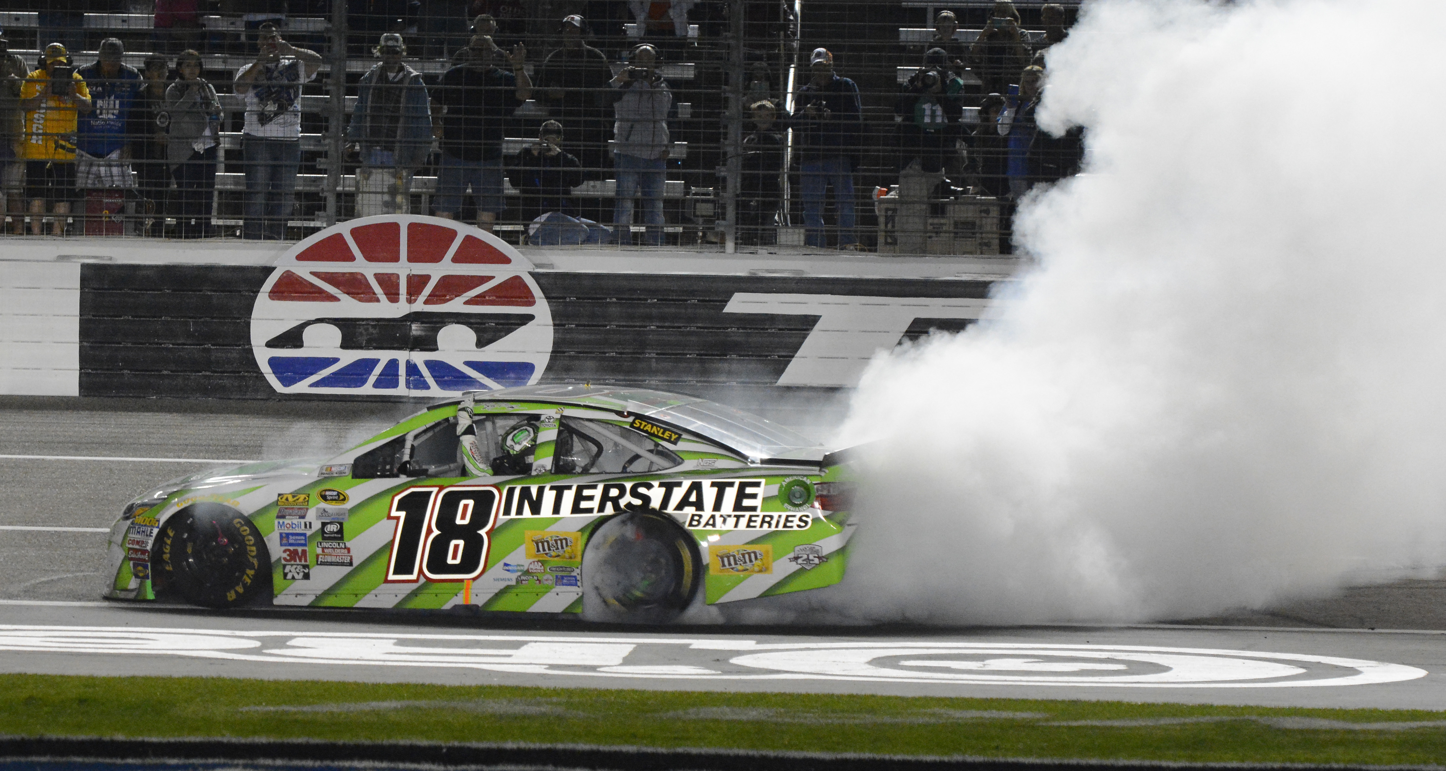 Kyle Busch does a burnout after winning the NASCAR Sprint Cup Series auto race at Texas Motor Speedway in Fort Worth, Texas, early Sunday, April 10, 2016. (AP Photo/Larry Papke)