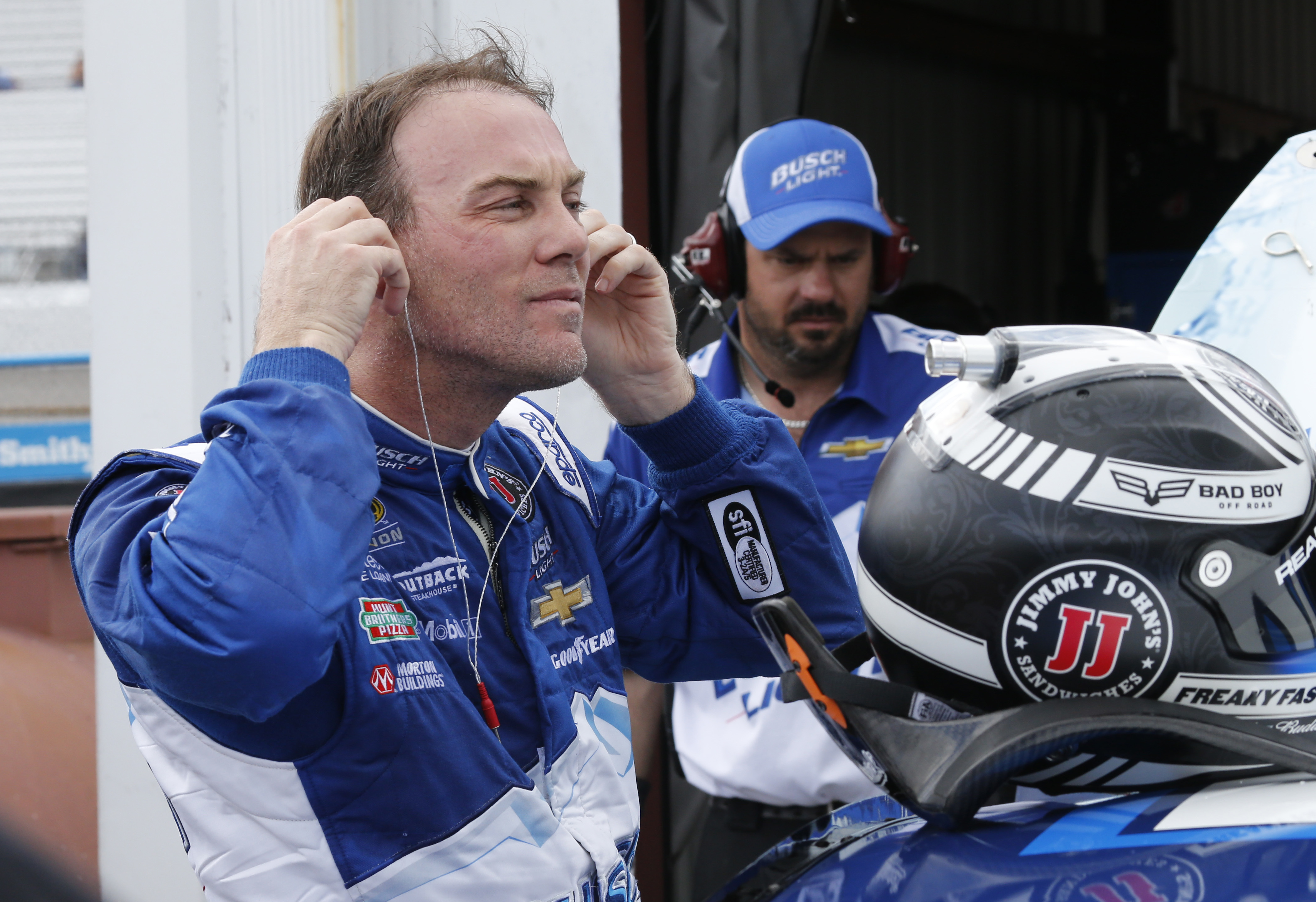 Kevin Harvick takes his earplugs out as he arrives in the garage after practice for Sunday's NASCAR Sprint Cup auto race at Richmond International Raceway in Richmond, Va., Saturday, April 23, 2016. Harvick has the pole for Sunday's race. (AP Photo/Steve