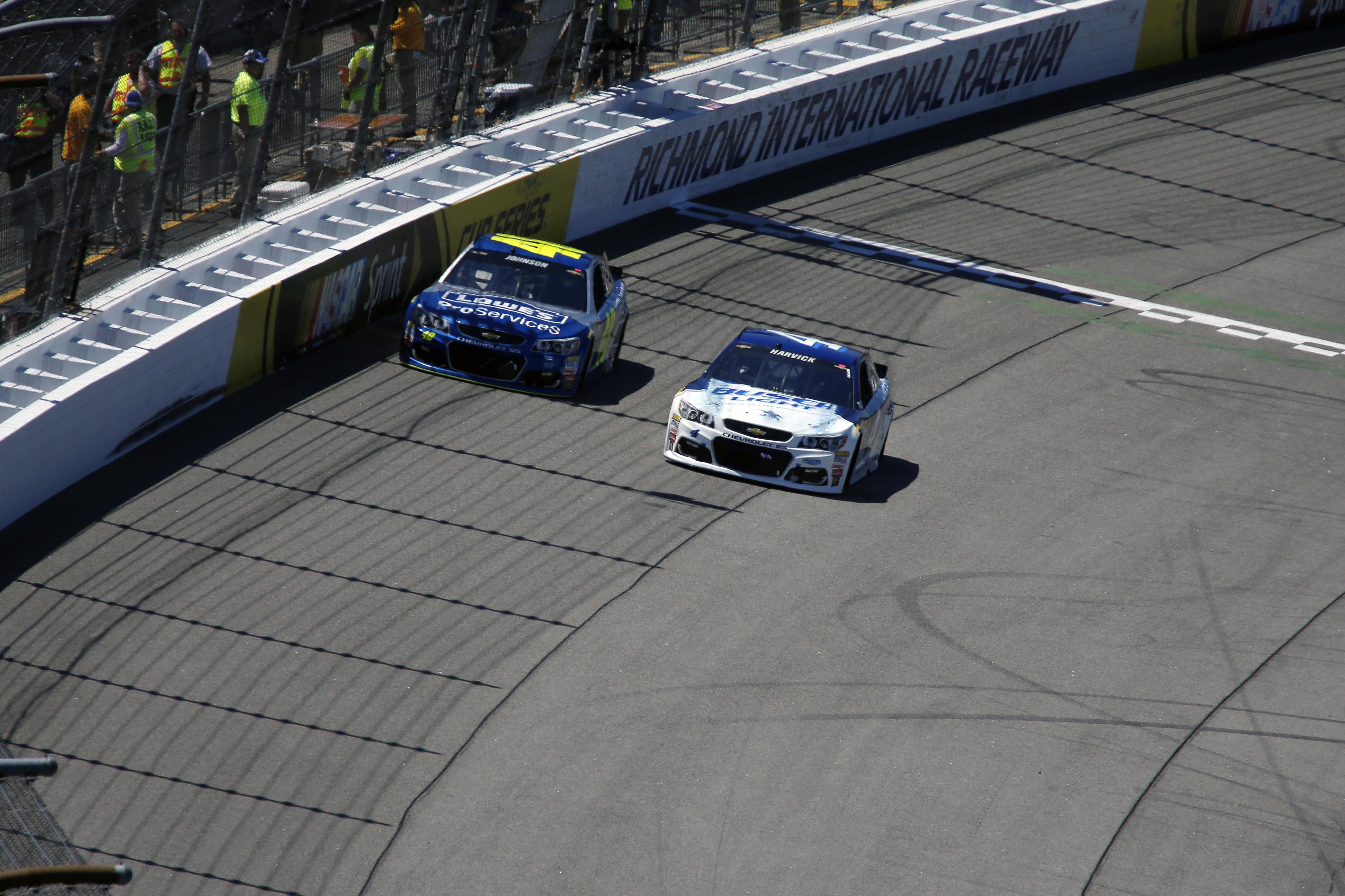 Jimmie Johnson, left, and Kevin Harvick round Turn 1 during the Sprint Cup auto race at Richmond International Raceway in Richmond, Va., Sunday, April 24, 2016. (AP Photo/Chet Strange)