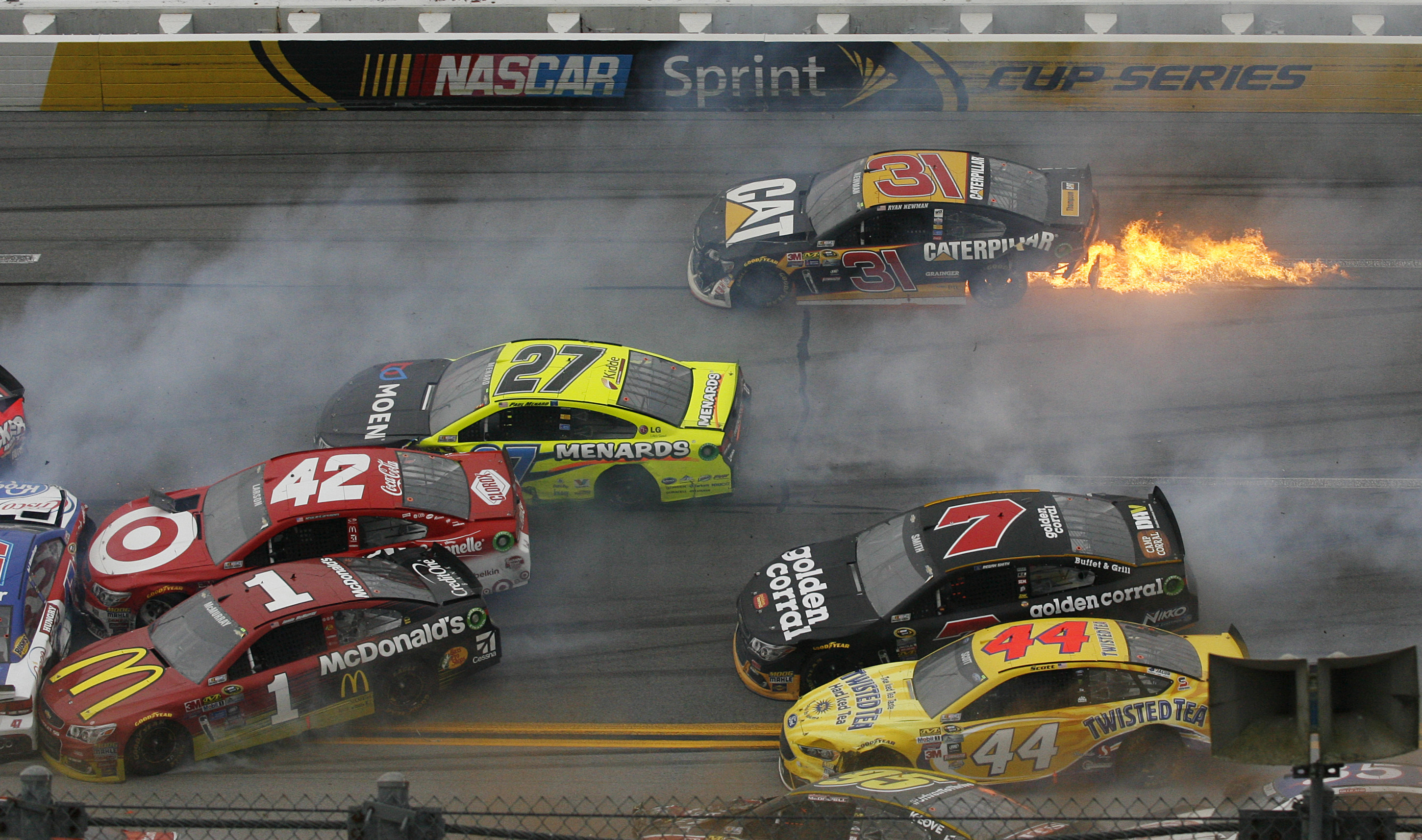 Flames trail from the car of Ryan Newman (31) after a pileup of crashed cars around the track during the NASCAR Talladega auto race at Talladega Superspeedway, Sunday, May 1, 2016, in Talladega, Ala. (AP Photo/Skip Williams)