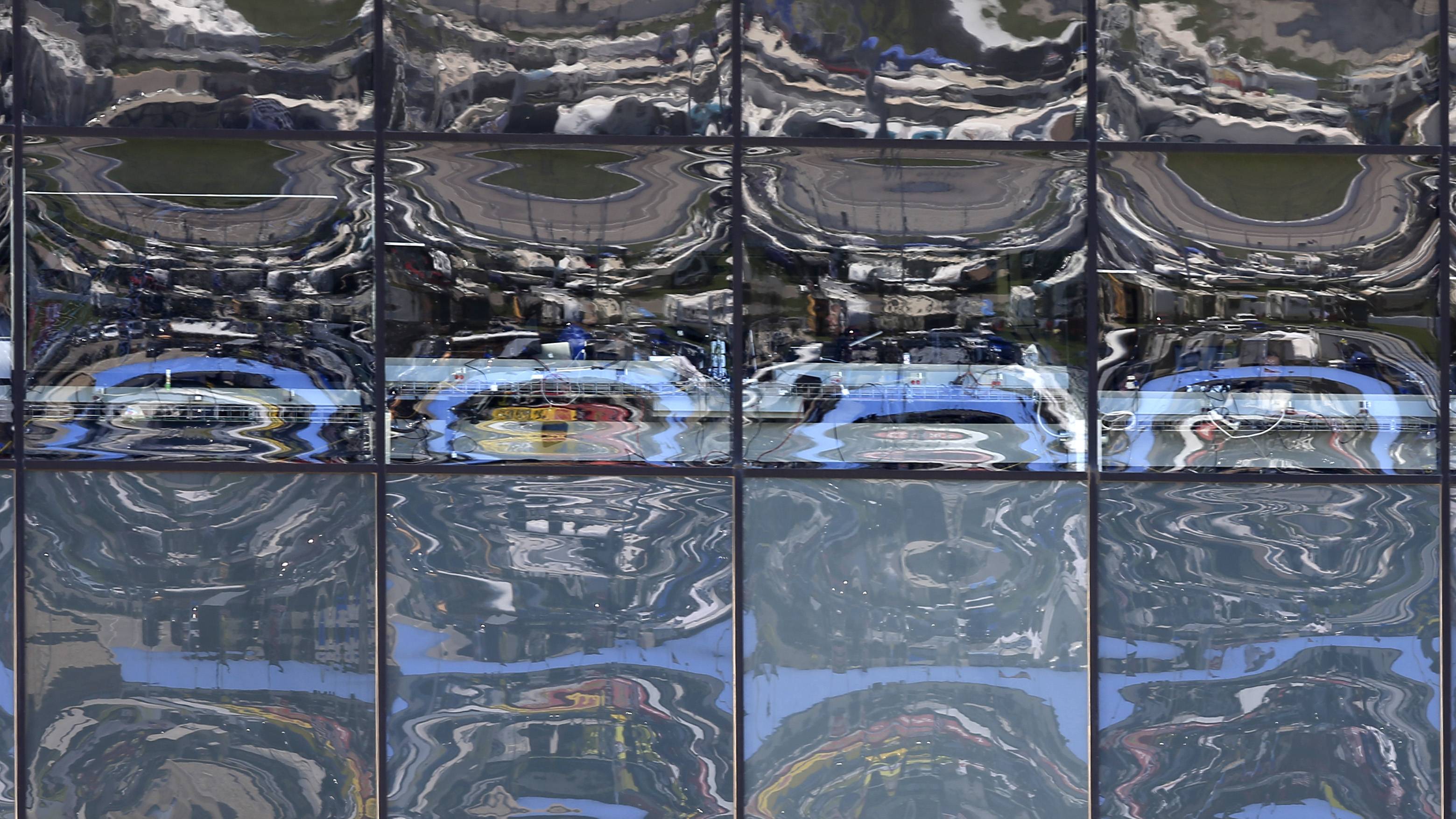 Scenes of the race track are reflected in the press box windows during NASCAR auto racing Sprint Cup Series practice at Kansas Speedway in Kansas City, Kan., Friday, May 6, 2016. (AP Photo/Orlin Wagner)