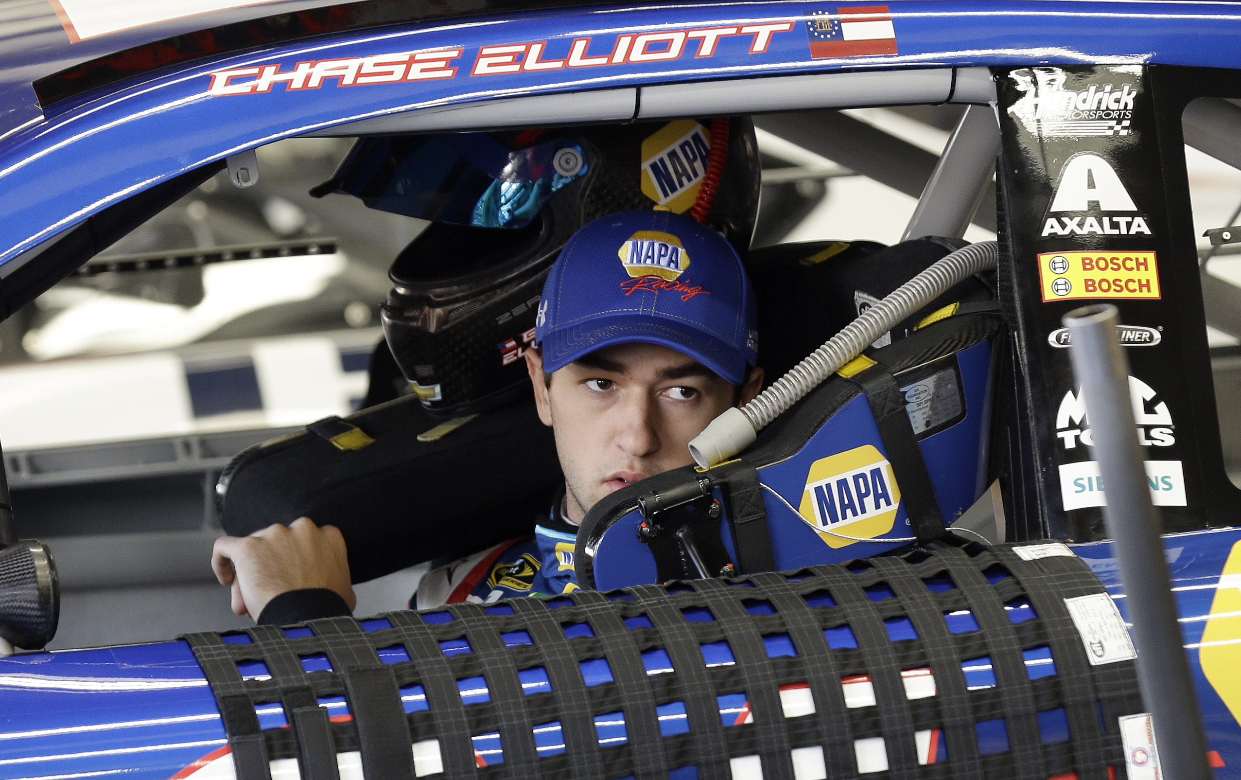 Chase Elliott waits in his car prior to practice for Sunday's NASCAR Sprint Cup Series auto race at the Charlotte Motor Speedway in Concord, N.C., Saturday, May 28, 2016. (AP Photo/Gerry Broome)