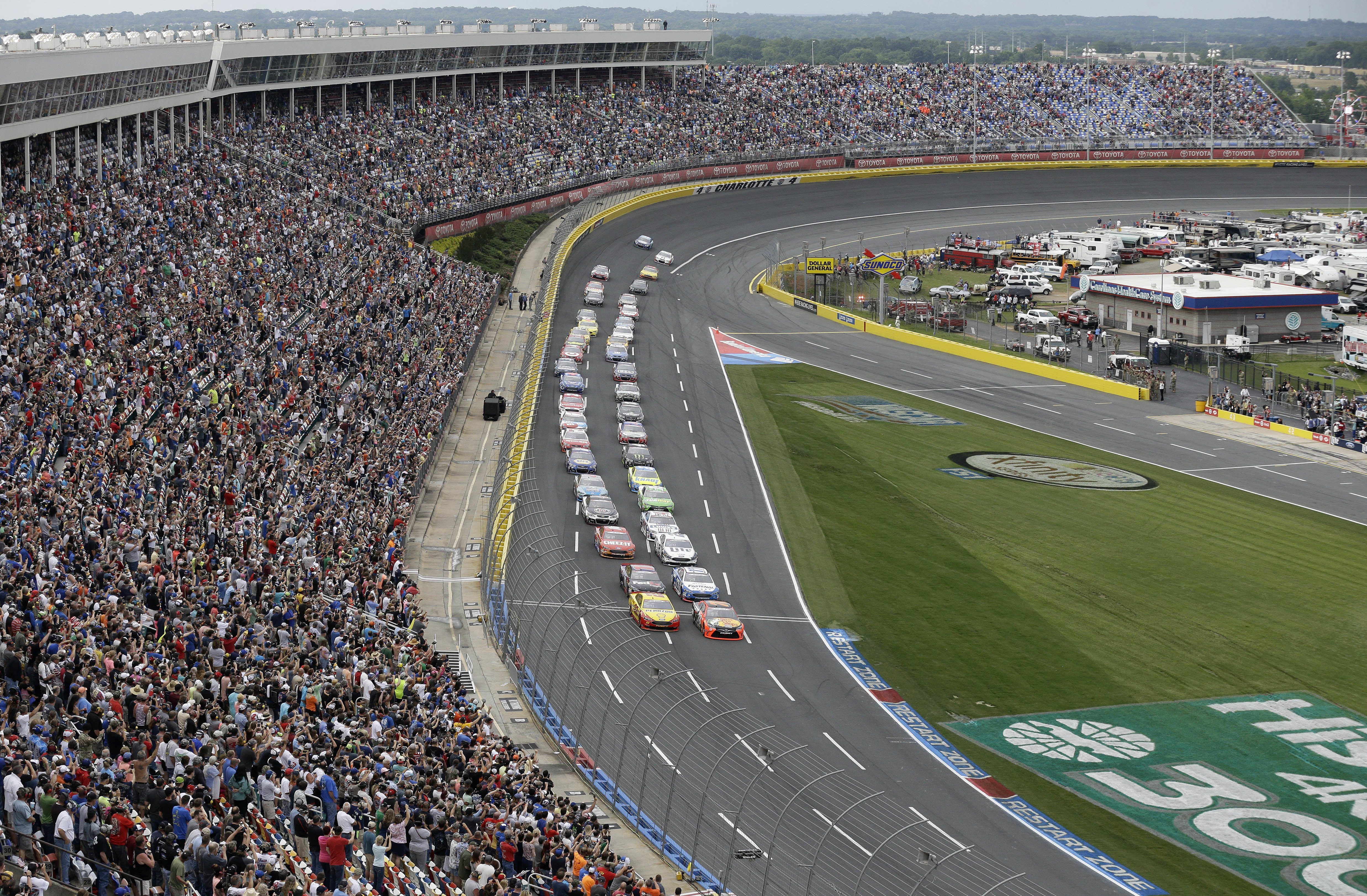 Cars drive along the front stretch as they approach the start-finish line to begin the NASCAR Sprint Cup Series auto race at the Charlotte Motor Speedway in Concord, N.C., Sunday, May 29, 2016. (AP Photo/Gerry Broome)