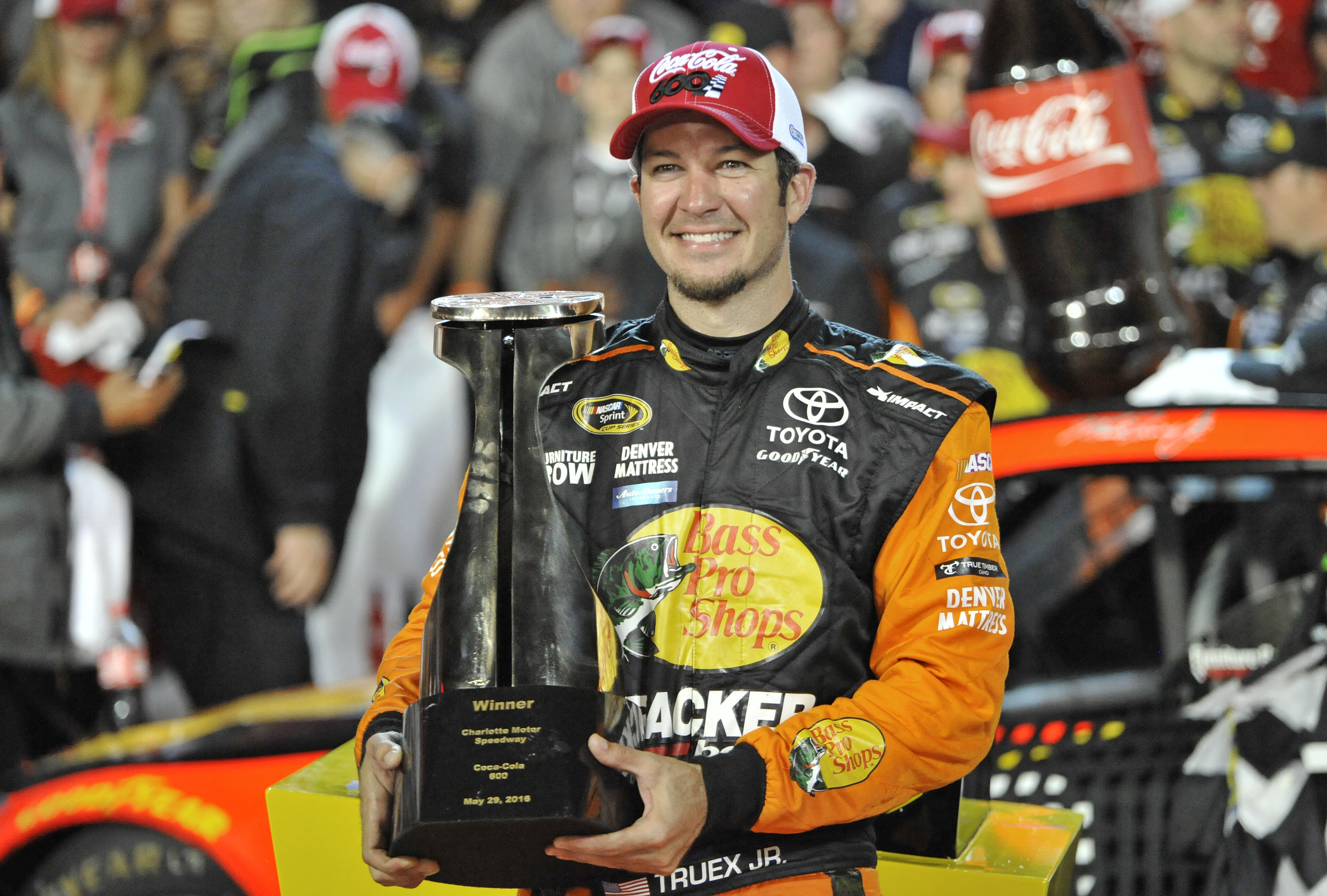 Martin Truex Jr poses with the trophy after winning the NASCAR Sprint Cup series auto race at Charlotte Motor Speedway in Concord, N.C., Sunday, May 29, 2016. (AP Photo/Matthew Bishop)