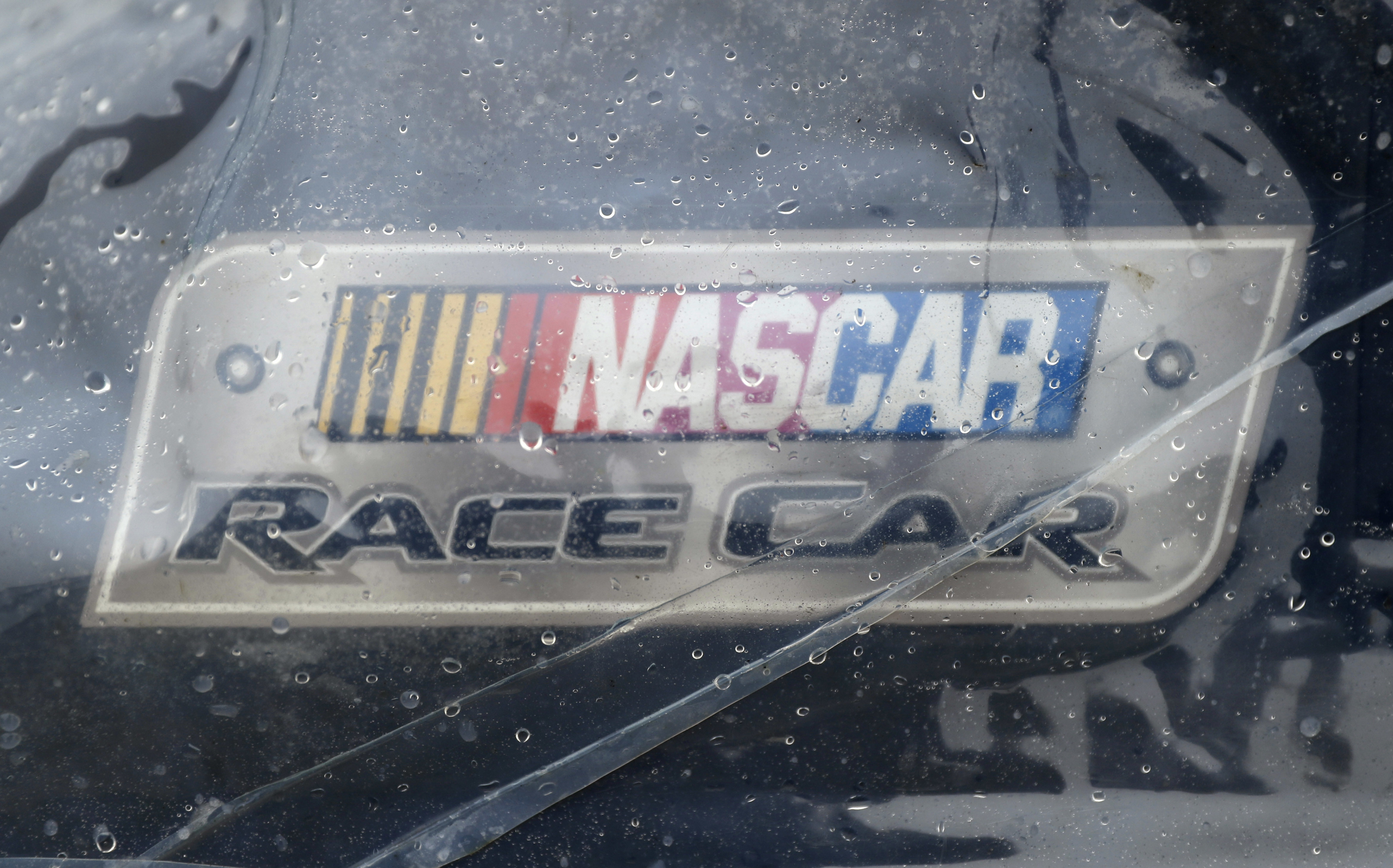 Rain drops are seen on a tarp over the car of Regan Smith before the NASCAR Sprint Cup series auto race, Sunday, June 5, 2016, in Long Pond, Pa. (AP Photo/Matt Slocum)
