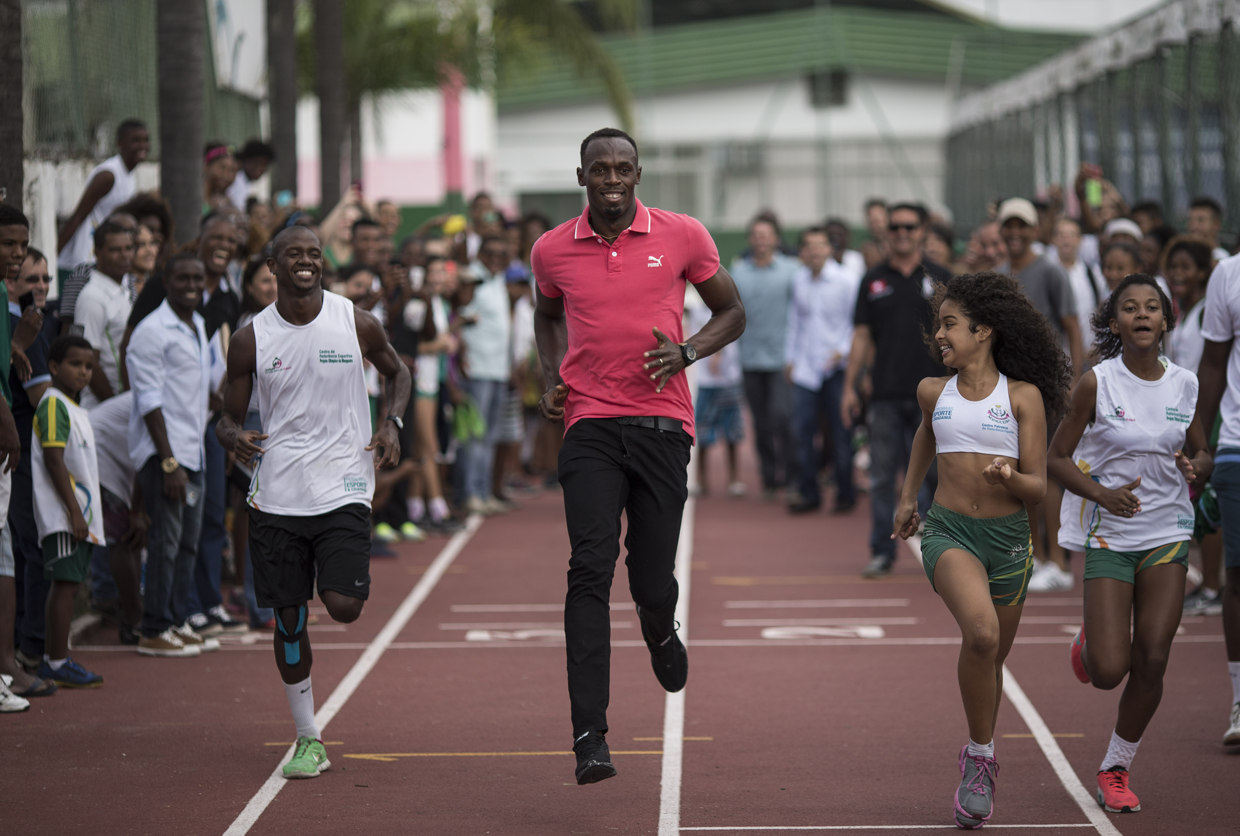 Jamaican Olympic gold medalist Usain Bolt, center, playfully races with youths during a visit to a social sport program at Mangueira slum in Rio de Janeiro, Brazil, Thursday, April 16, 2015. (AP Photo/Felipe Dana)