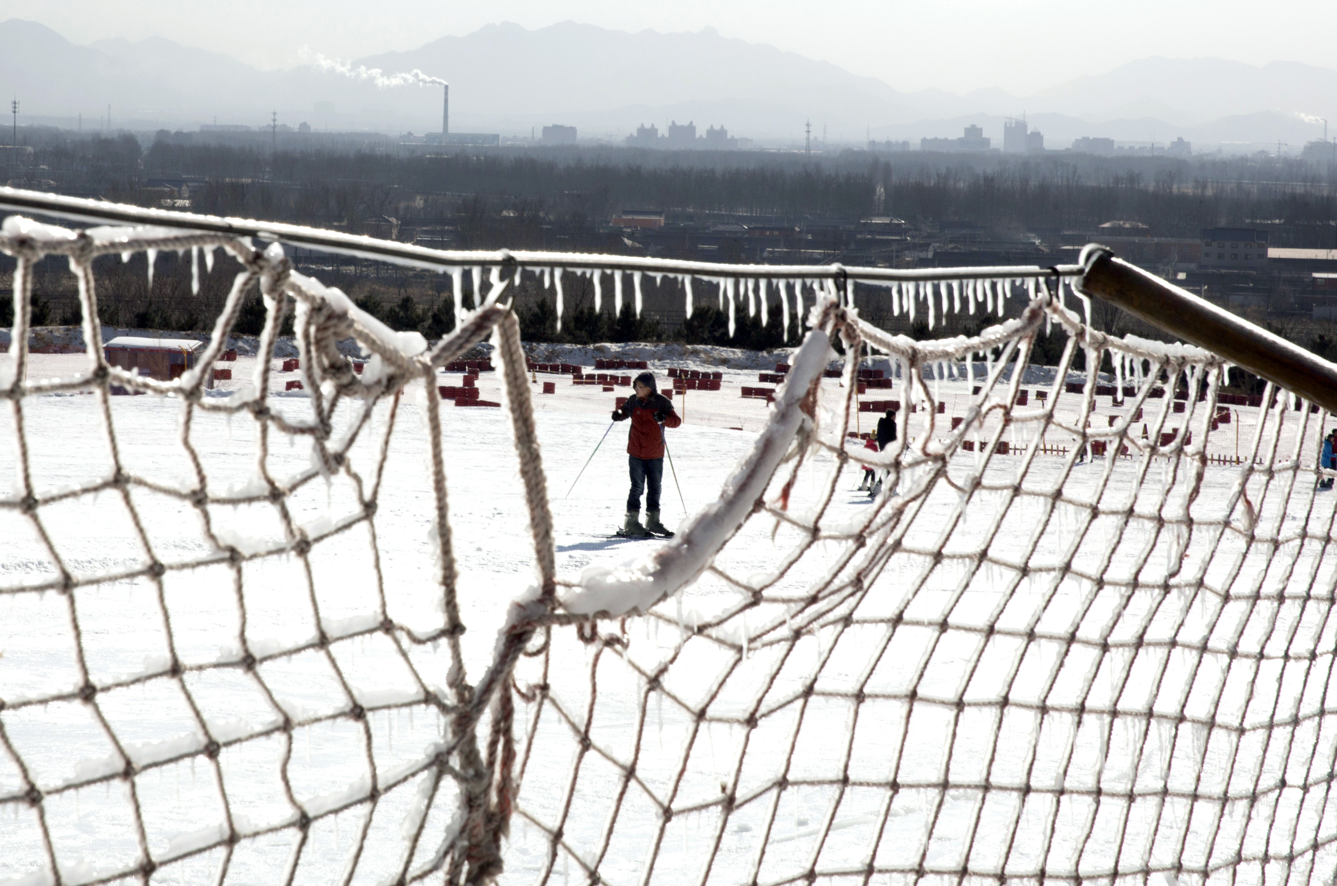 In this photo taken Friday, Jan. 16, 2015, a man prepares to ski at a resort in Yanqing, a suburb of Beijing, where the speed mavens of Alpine skiing and the sliding events - bobsled, skeleton and luge - have been proposed to be held in the bid for the 20