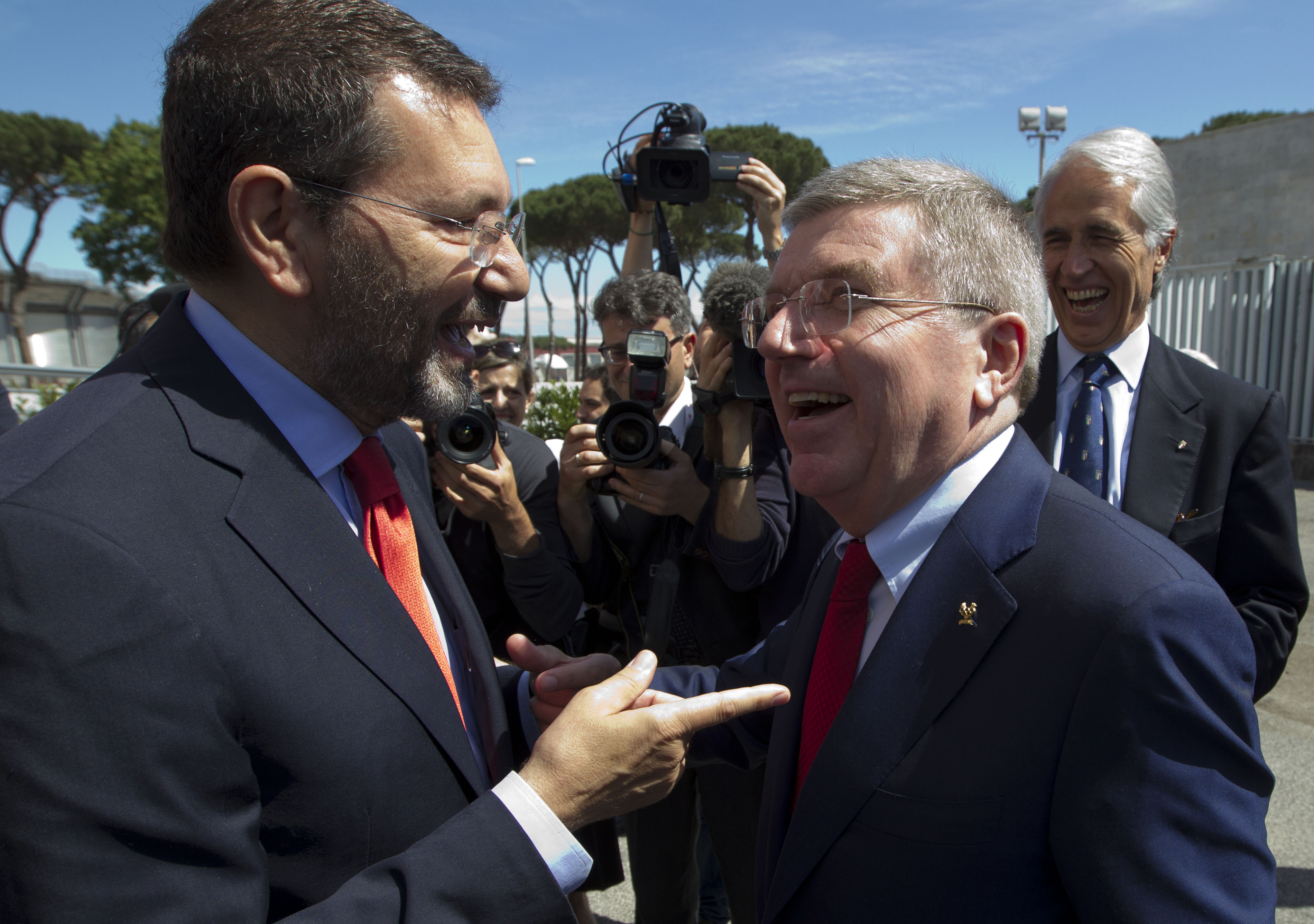FILE - In this Friday, May 22, 2015 file photo, International Olympic Committee, IOC, president Thomas Bach, right, is greeted by Rome's mayor Ignazio Marino as he arrives to visit the Rome 2024 Olympic bid headquarters, in Rome. Rome's city council Thurs