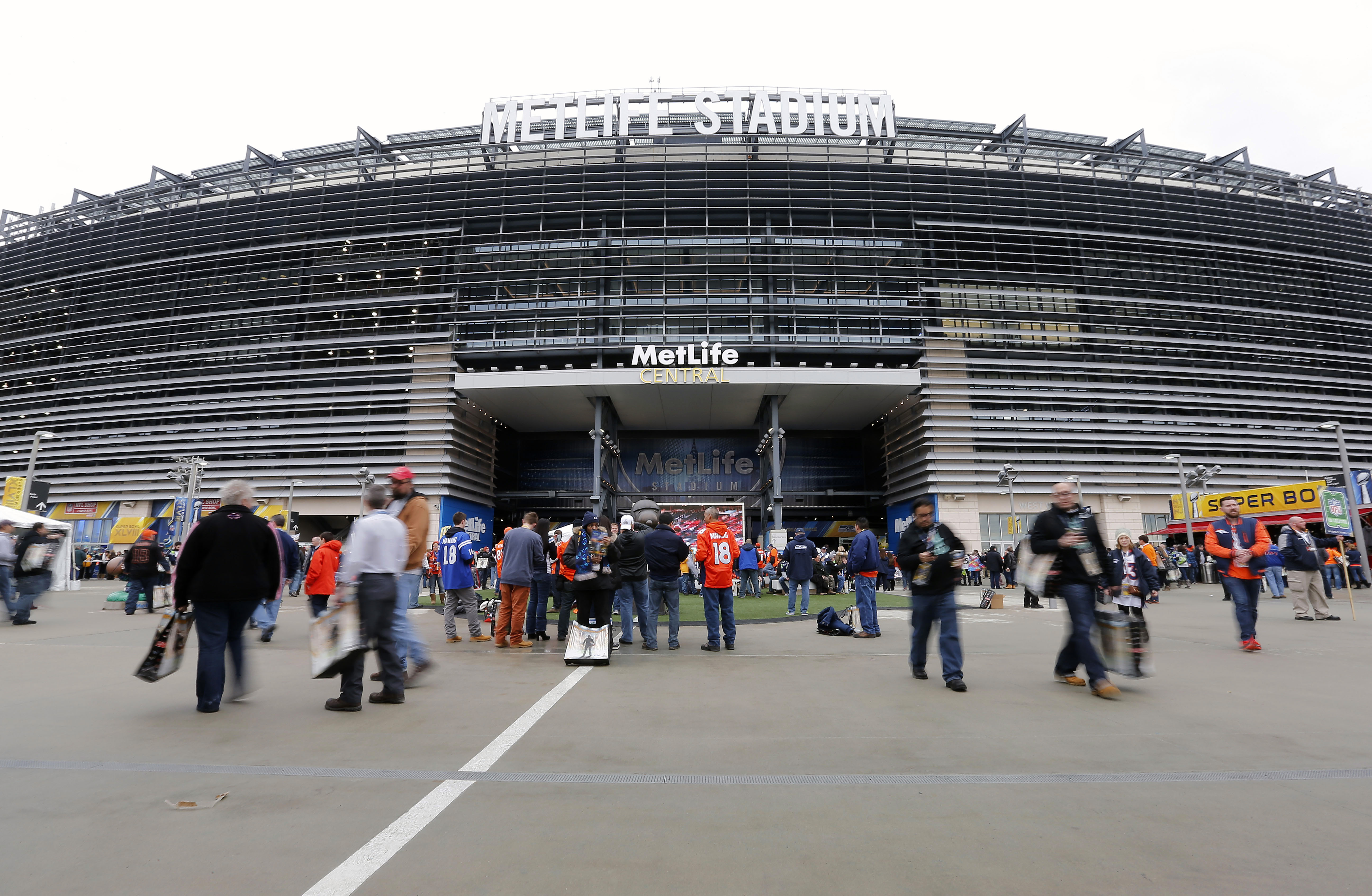FILE - In this Feb. 2, 2014 file photo, fans arrive outside MetLife Stadium before the NFL Super Bowl XLVIII football game between the Seattle Seahawks and the Denver Broncos in East Rutherford, N.J.  The latest cost of the new National Stadium for the 20