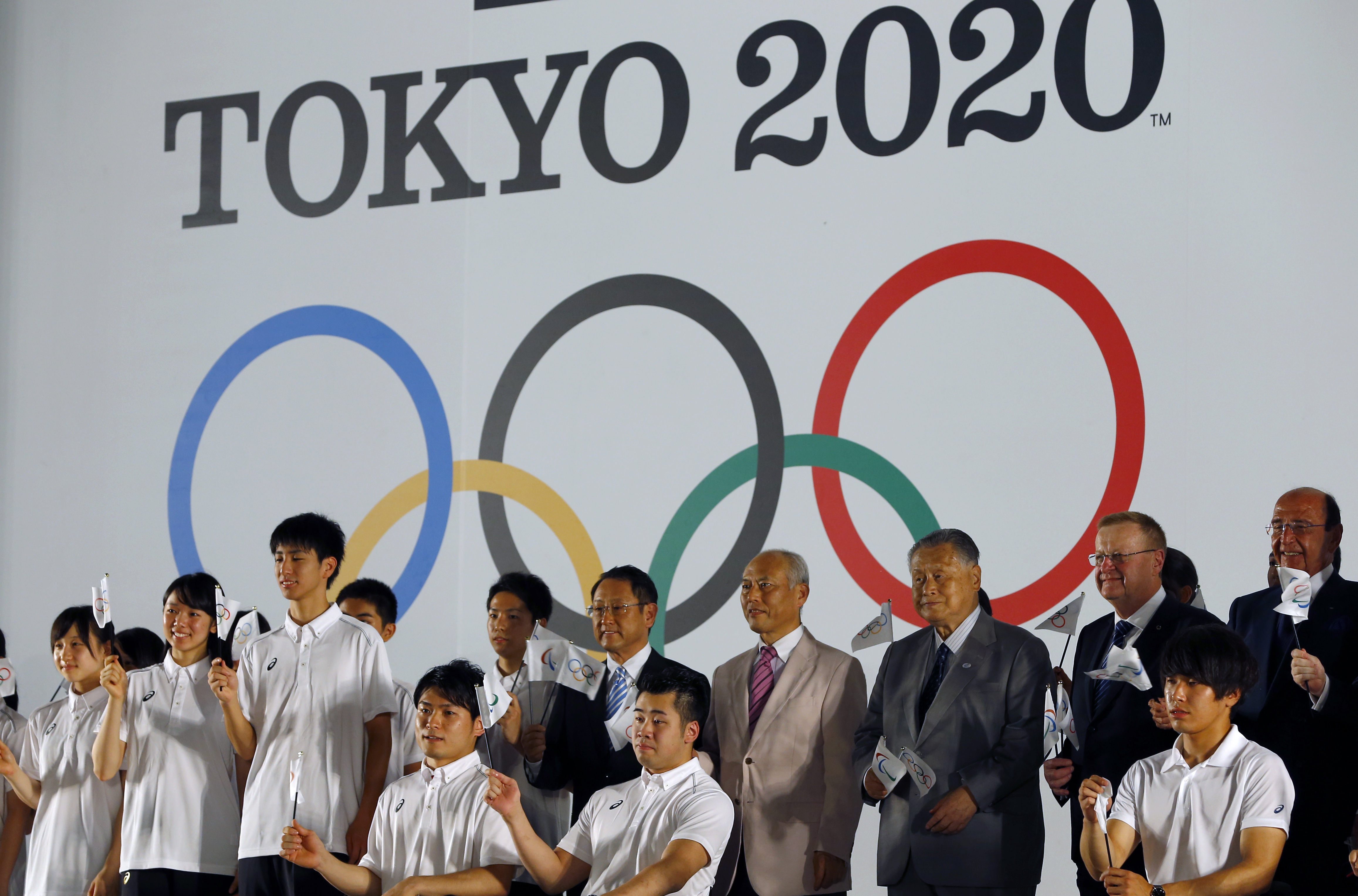 International Olympic Committee Vice President John Coates, second right, and Tokyo 2020 Summer Olympic Organizing Committee President Yoshiro Mori third right, pose for photographers in front of official emblems of the Tokyo 2020 Olympic Games at Tokyo M