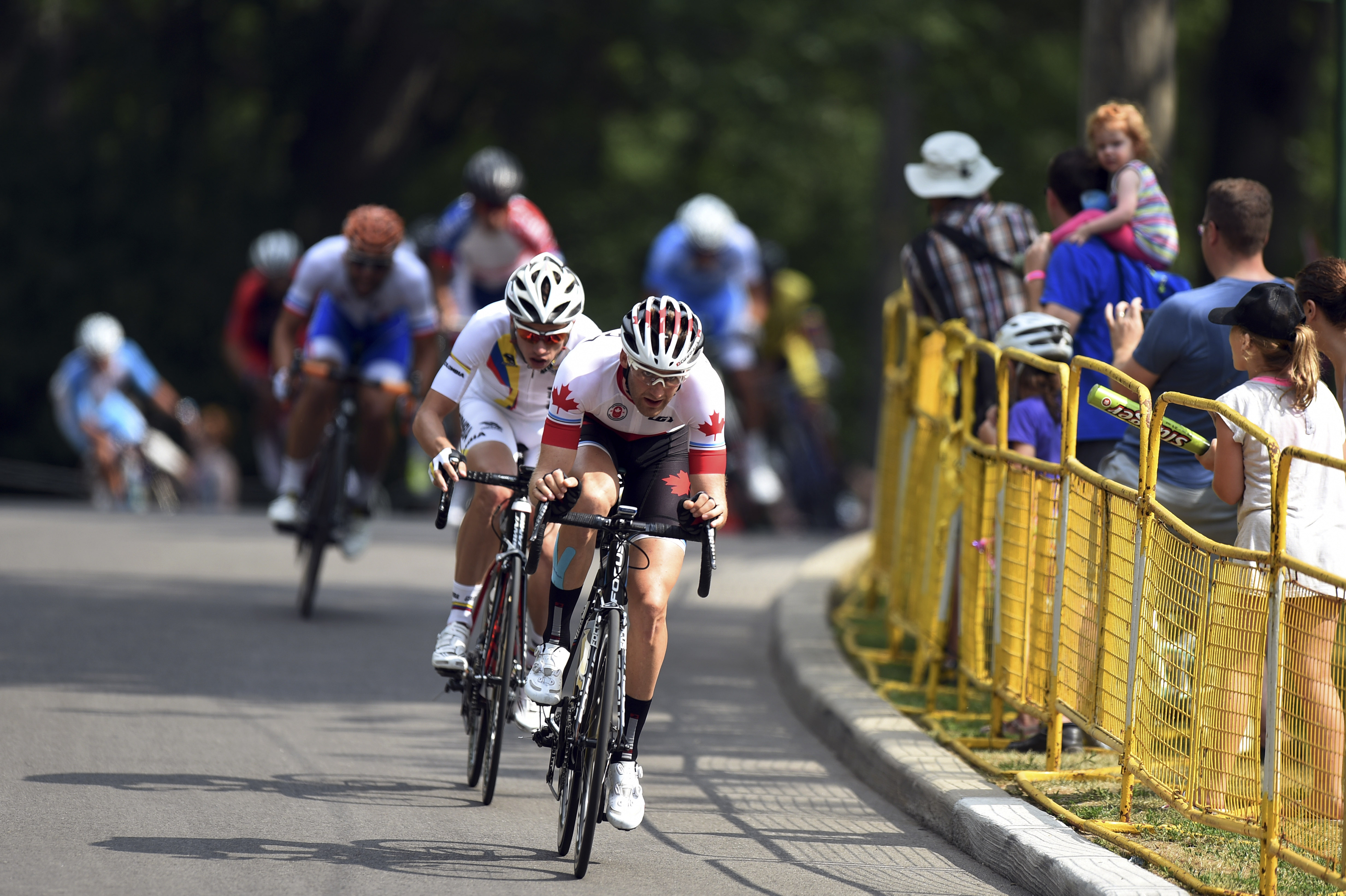 Cyclists compete in the peloton during the men's cycling road race at the 2015 Pan Am Games in Toronto, Saturday, July 25, 2015.  (Hector Retamal, Pool photo via AP)