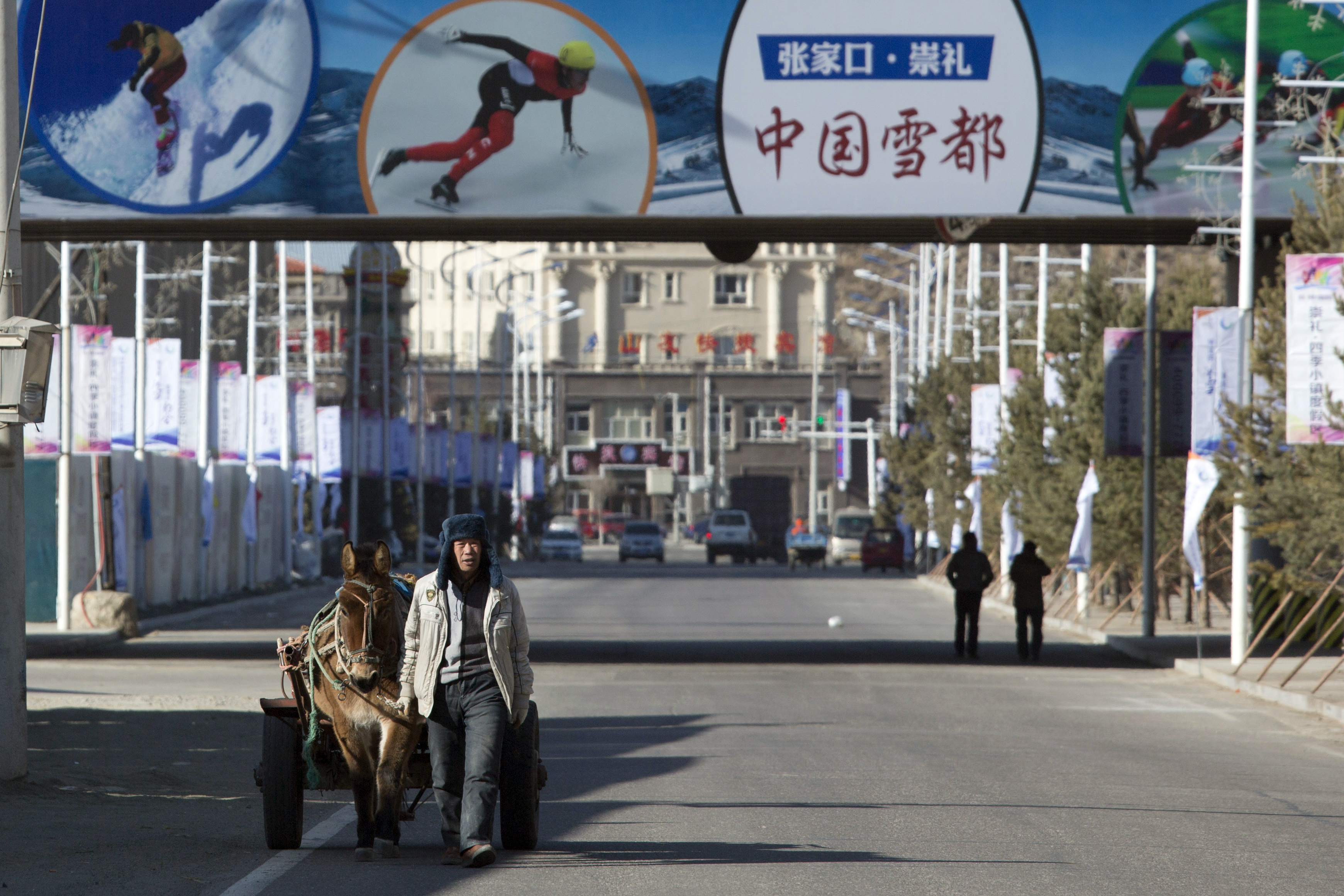 In this photo taken Sunday, Dec. 7, 2014, a man leads a mule pulling a cart past publicity billboard promoting Zhangjiakou, Chongli as the snow capital of China near the Chongli ski area outside Beijing.  Beijing has marketed its bid for the 2022 Winter O
