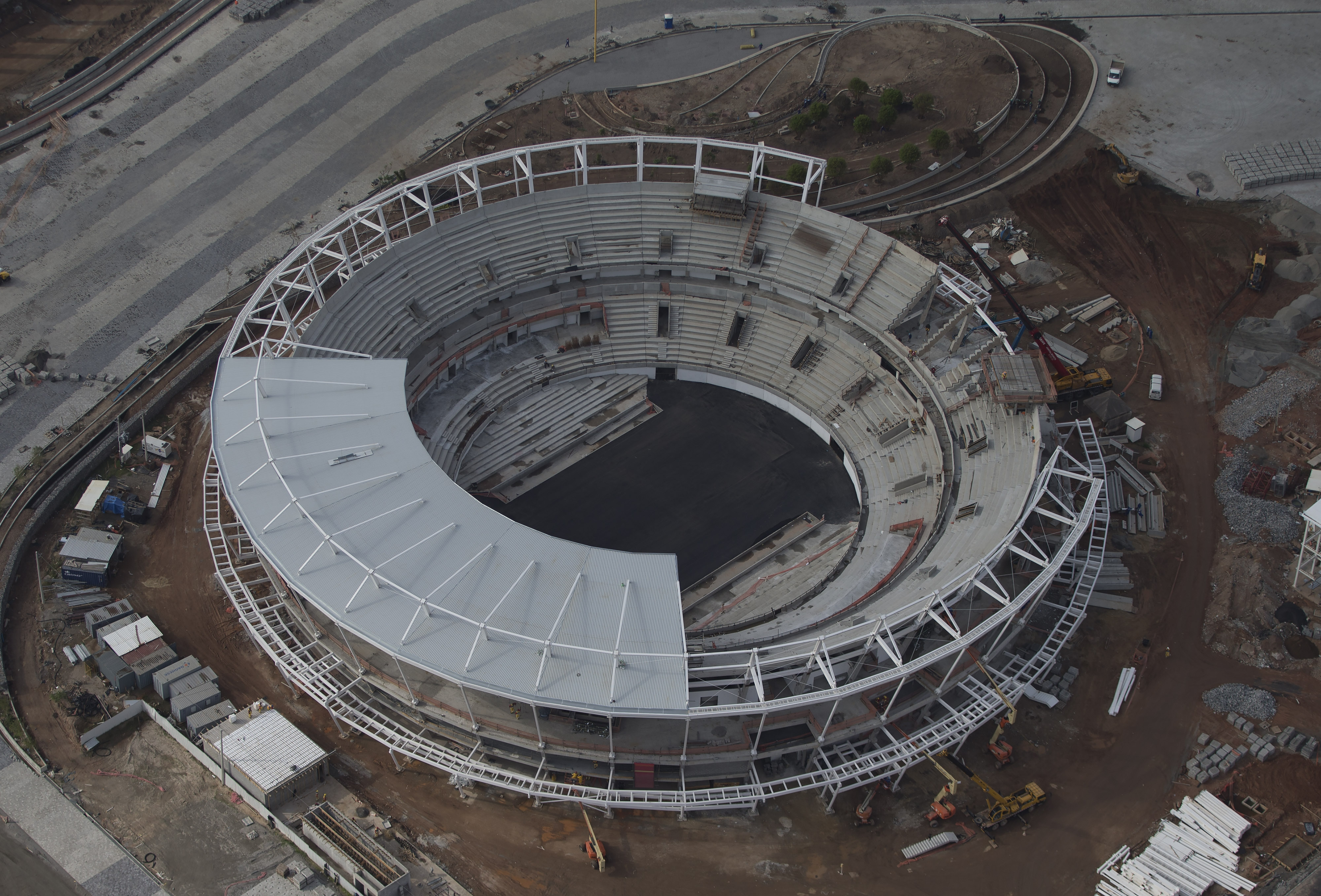 Construction continues at the Tennis Center at the Olympic Park for the 2016 Olympics in Rio de Janeiro, Brazil, Monday, July 27, 2015. A last-minute rush seems inevitable, and late work is sure to drive up costs. (AP Photo/Leo Correa)