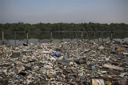 In this May 15, 2014 photo, trash floats on a polluted water channel that flows into the Guanabara Bay in Rio de Janeiro, Brazil. In its 2009 Olympic bid, officials promised that the city's waterways would be cleaned up but Brazil will not make good on it