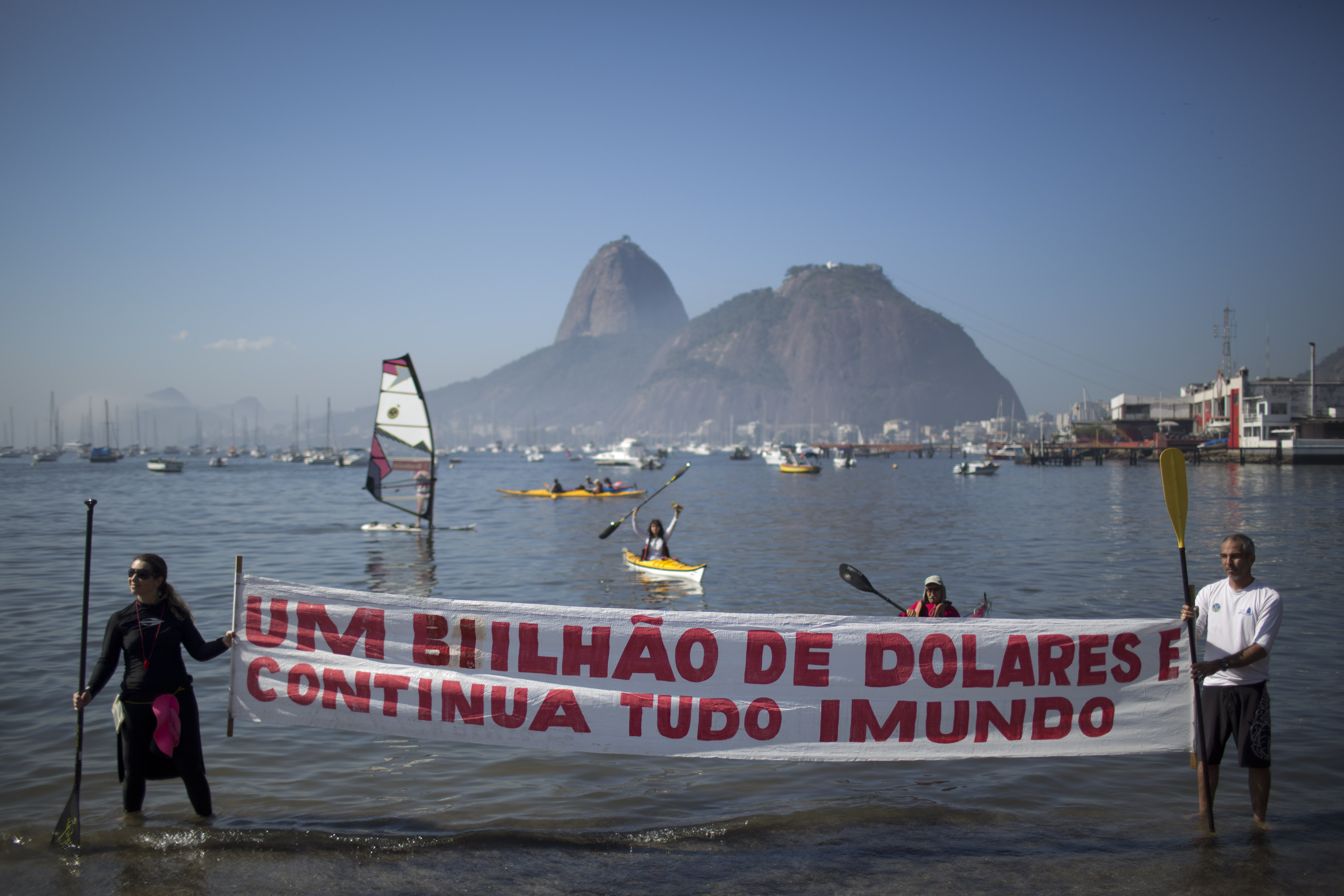 "Protesters hold a banner with a message that reads in Portuguese; ""One billion dollars and it's still disgusting"" during a demonstration on Botafogo Beach, in the Guanabara Bay in Rio de Janeiro, Brazil, Saturday, June 6, 2015, near where Olympic sailin"